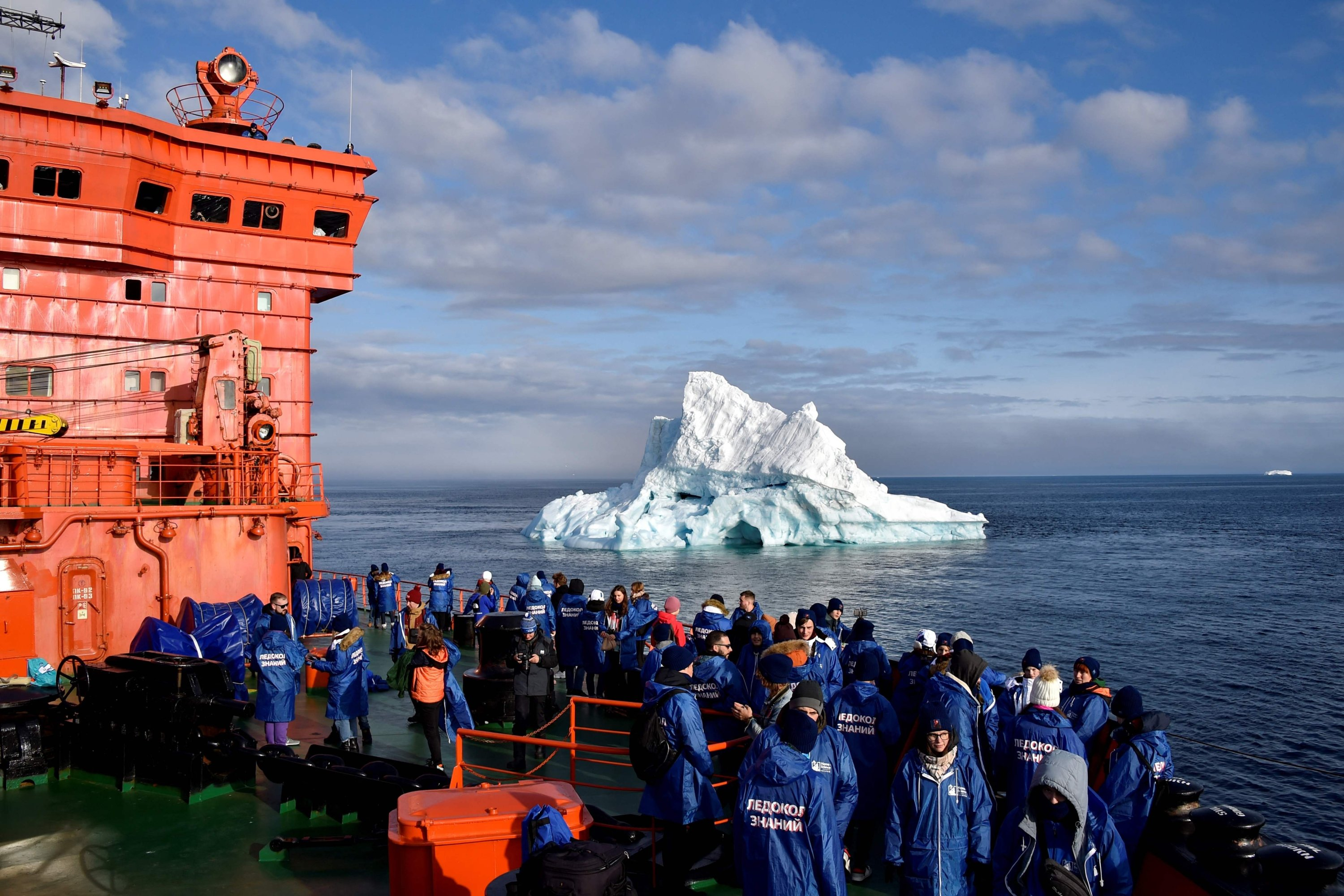 Russian teenagers who won a contest to travel aboard the Russian nuclear-powered icebreaker '50 Years of Victory' look at an iceberg in the Arctic Ocean from the deck of the 160-meter (525-foot) ship on Aug. 20, 2021. (AFP Photo)