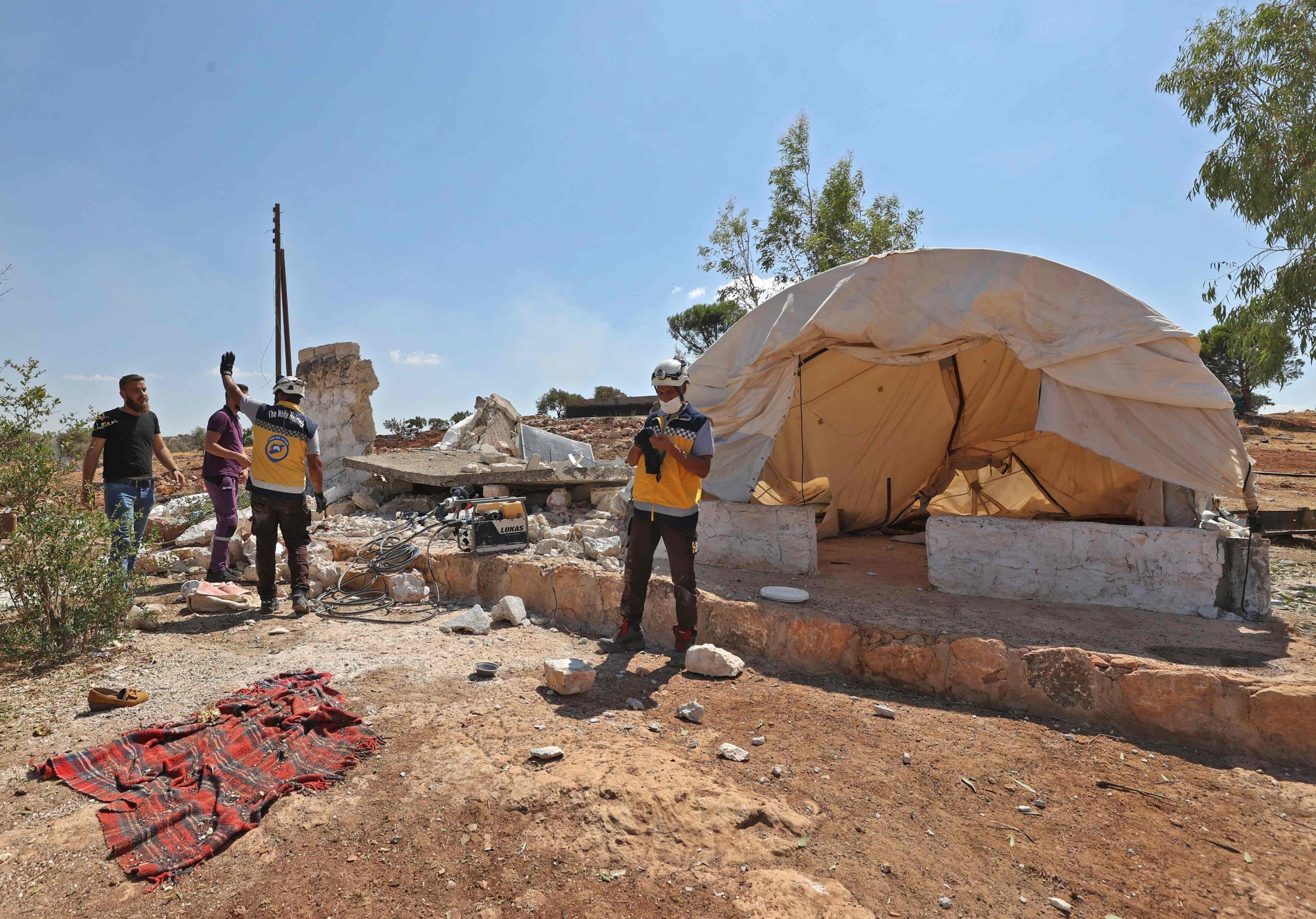 Members of White Helmets gather by a collapsed building at a tent in the aftermath of aerial bombardment at a makeshift camp for displaced Syrians near the town of Kafraya in the north of rebel-held Idlib province, Syria, Sept. 7, 2021. (AFP Photo)