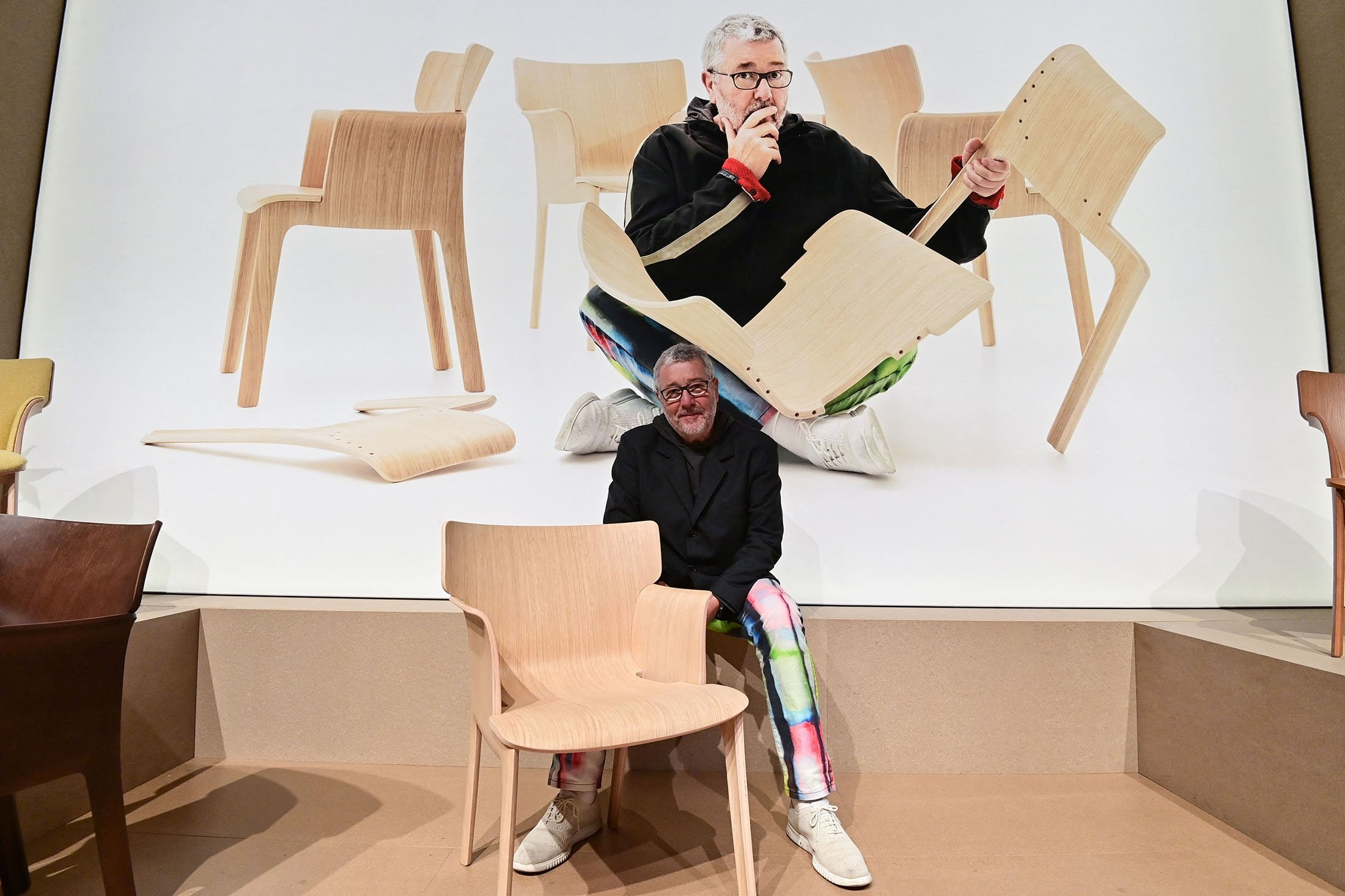 French designer Philippe Starck poses with one of the chairs he designed at the Andreu World stand, at the 2021 Salone del Mobile Milano, in Rho on the outskirts of Milan, Italy, Sept. 7, 2021. (AFP Photo)