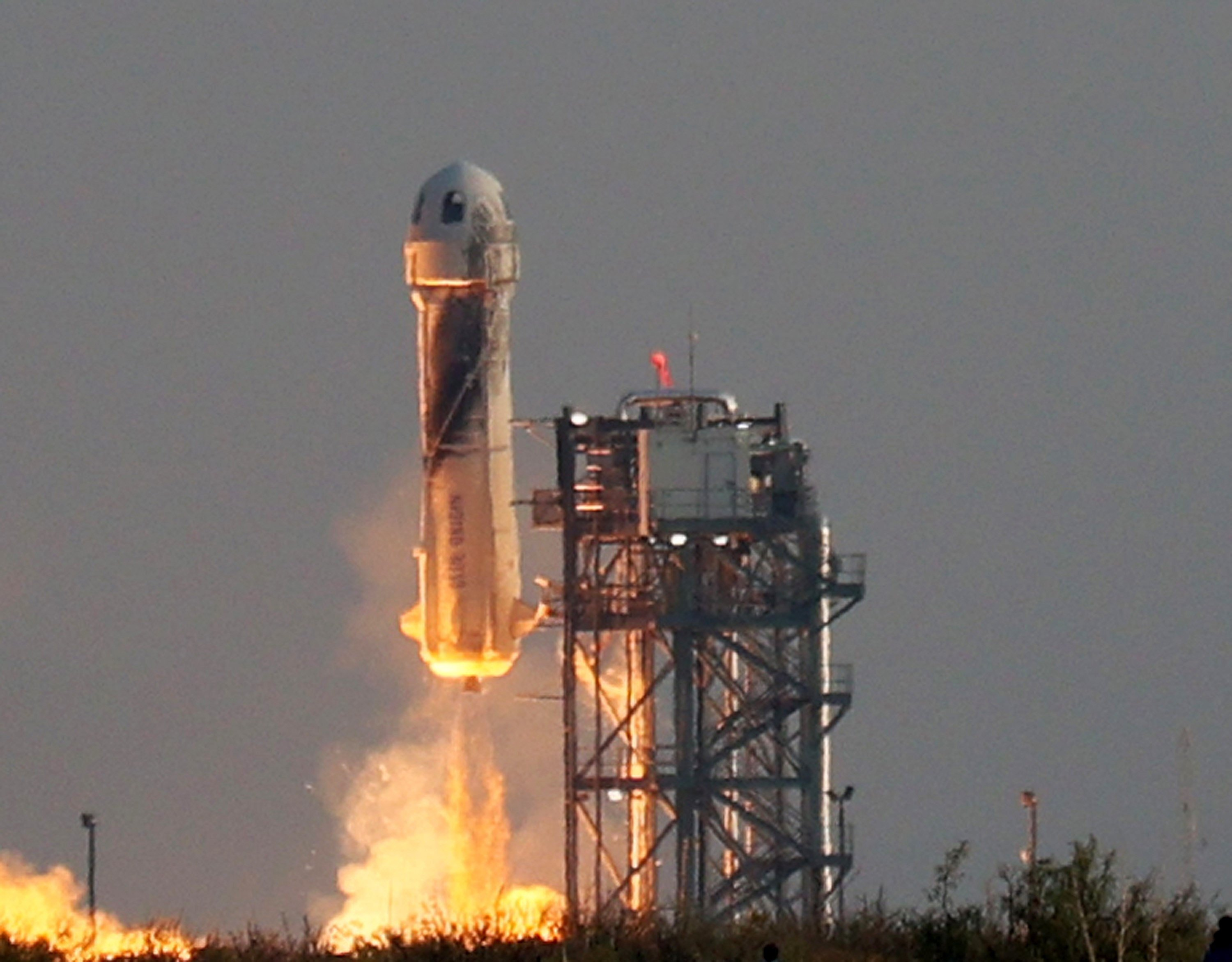 Blue Origin's New Shepard lifts off from the launch pad carrying Jeff Bezos along with his brother Mark Bezos, 18-year-old Oliver Daemen and 82-year-old Wally Funk, in Van Horn, Texas, U.S., July 20, 2021. (Joe Raedle/Getty Images via AFP)