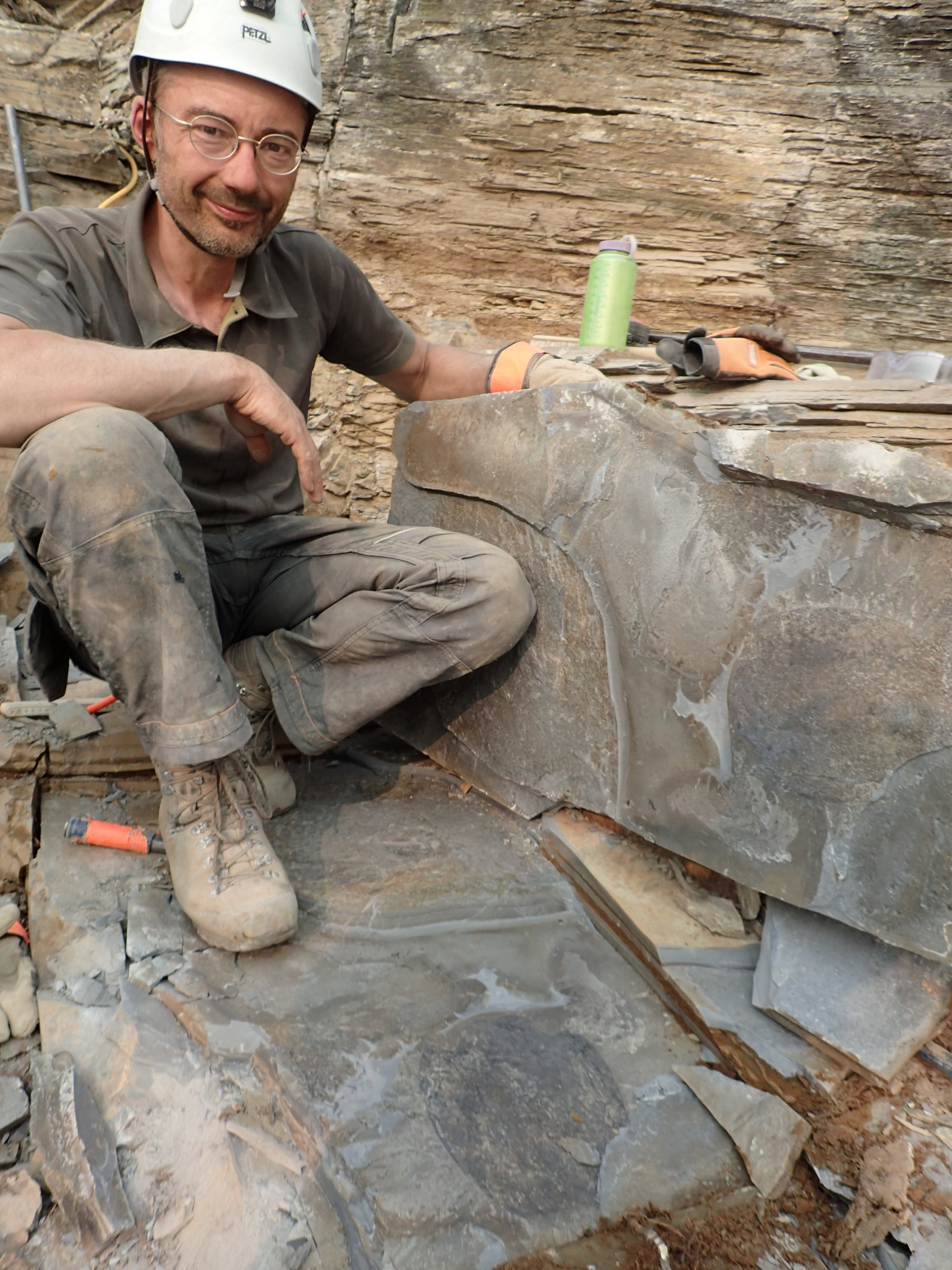 Paleontologist Jean-Bernard Caron of the Royal Ontario Museum sits above a fossil of Titanokorys gainesi at the quarry site located in Kootenay National Park, British Columbia, Canada, 2018. (Reuters Photo)