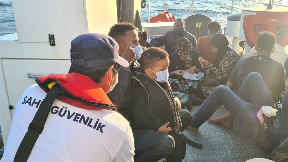 Turkish coast guard authorities in western Turkey's Kuşadası speak to rescued migrants after they were pushed back by Greek forces, Sept. 8, 2021. (IHA Photo)