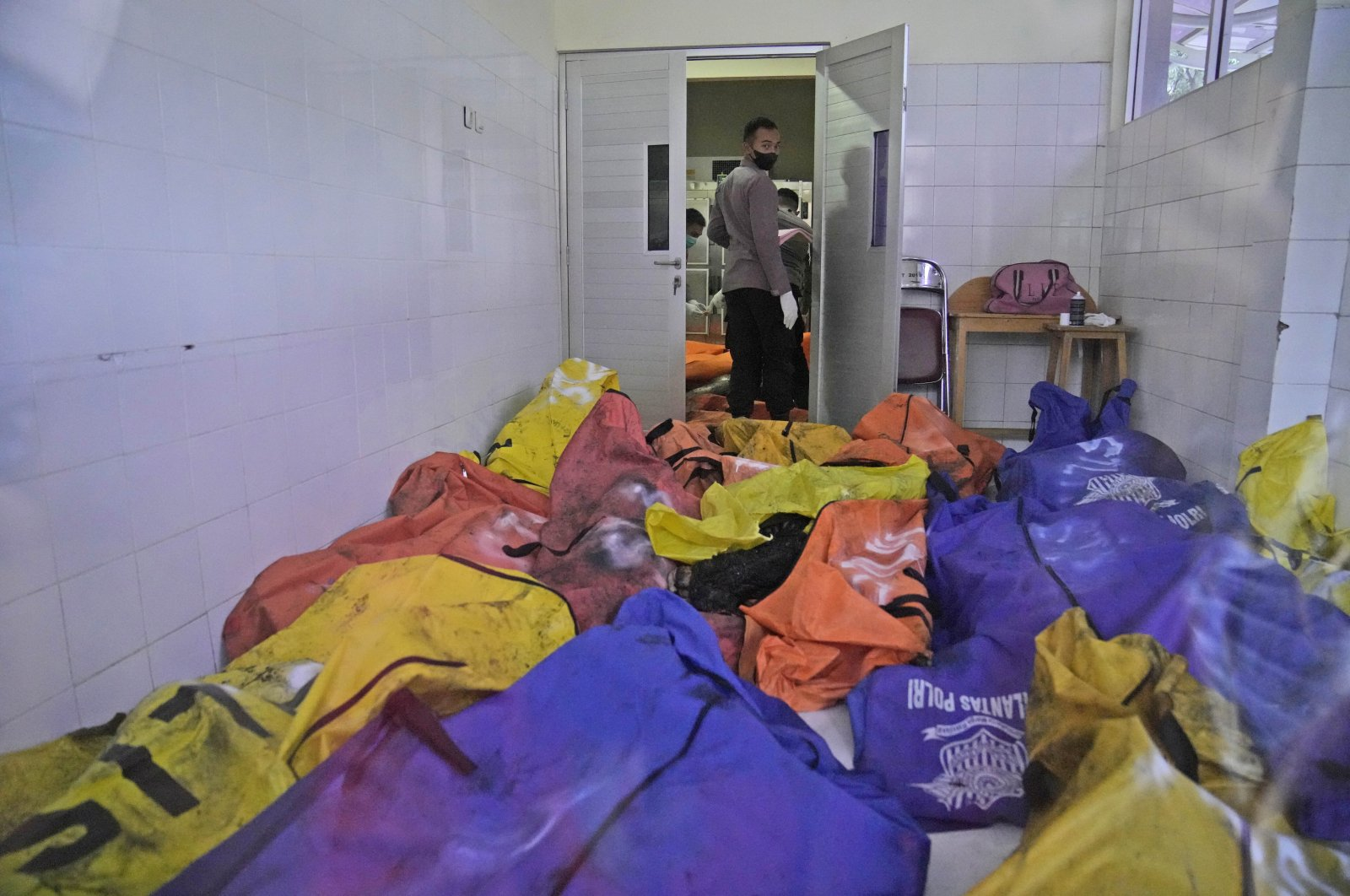 A police officer stands near body bags containing the bodies of the victims of a prison fire at the local hospital's morgue in Tangerang on the outskirts of Jakarta, Indonesia, Sept. 8, 2021. (AP Photo/Dita Alangkara)