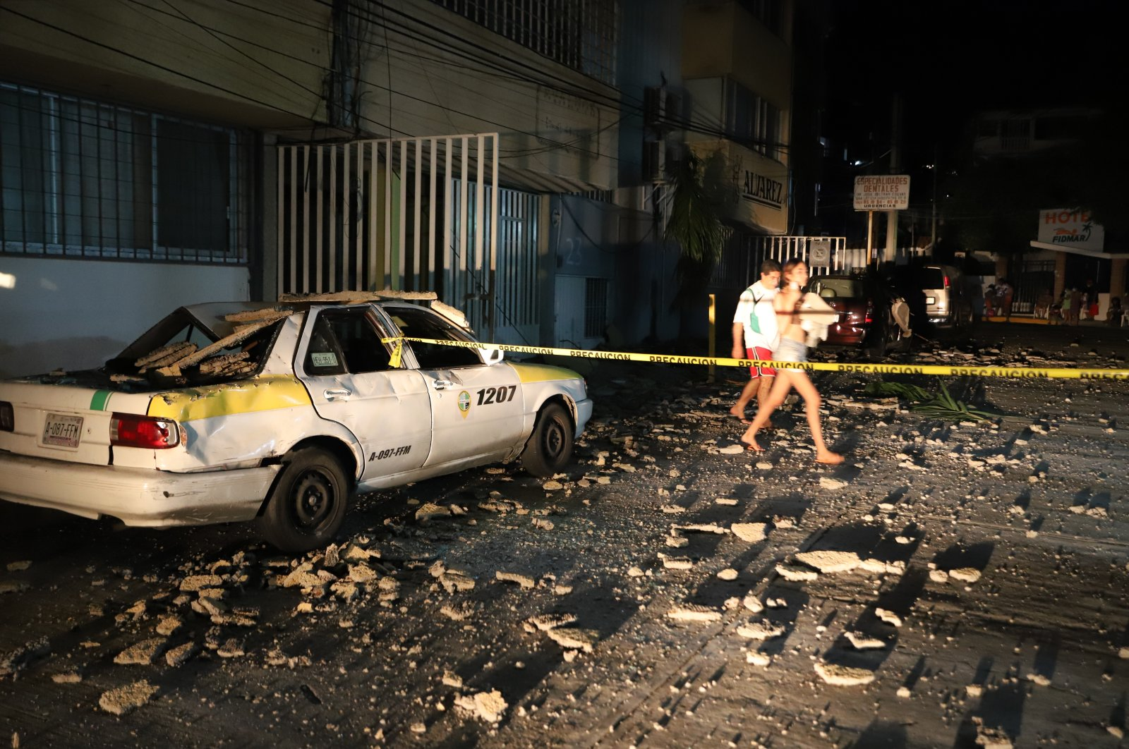 A couple walks past a taxi cab that was damaged by falling debris after a strong earthquake in Acapulco, Mexico, Sept. 7, 2021. (AP Photo)