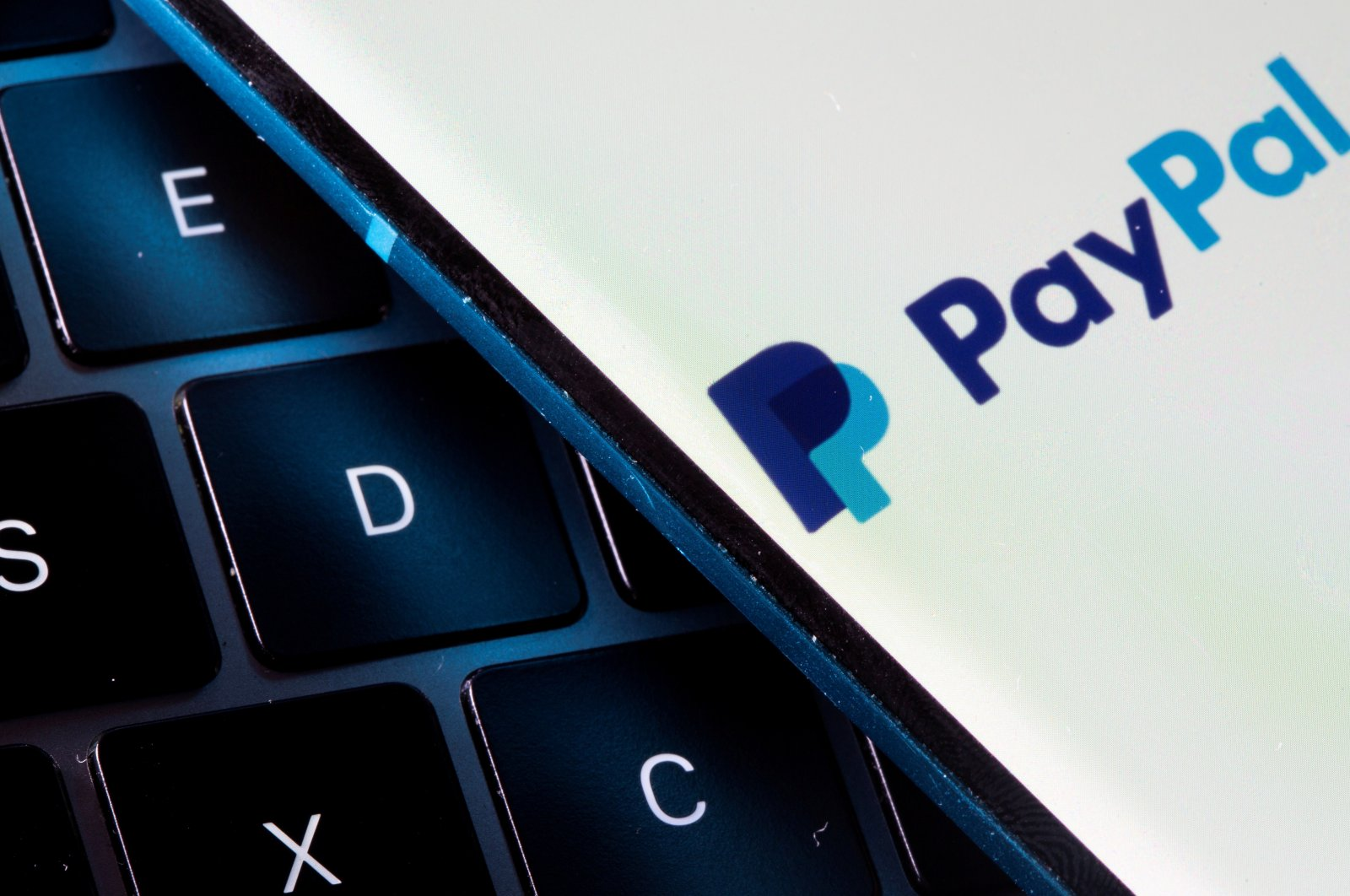 A smartphone with the PayPal logo is placed on a laptop in this illustration taken on July 14, 2021. (Reuters Photo)