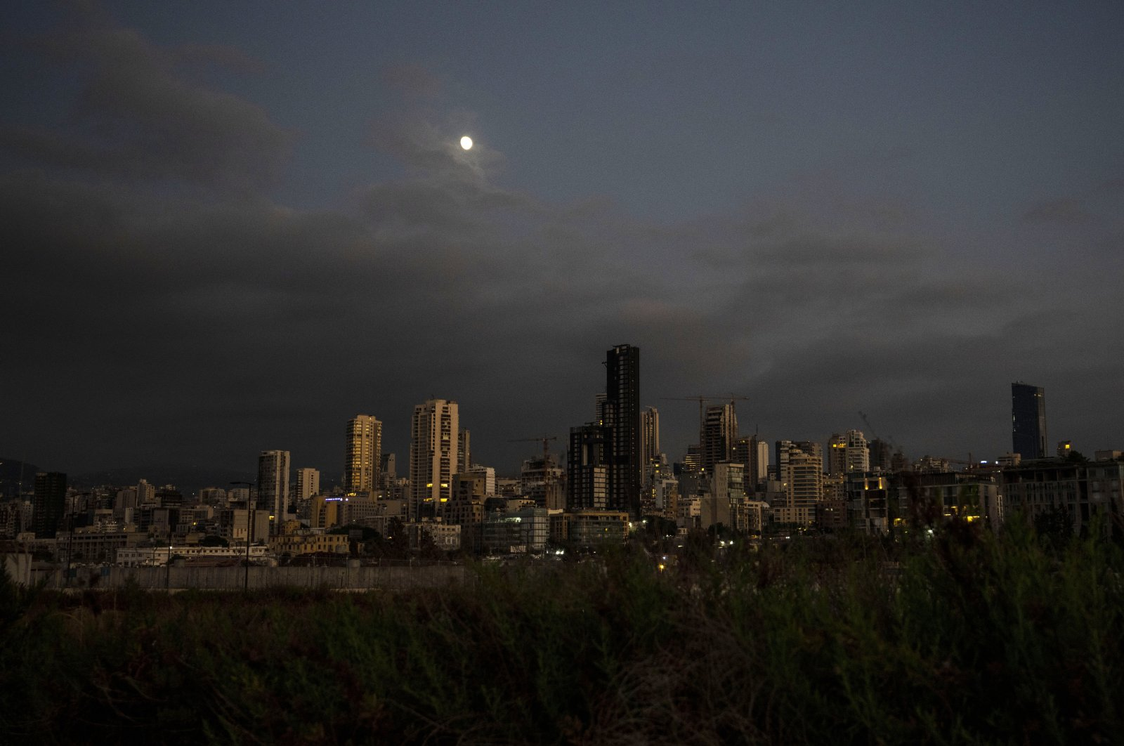 The moon rises over the capital city of Beirut as it remains in darkness during a power outage, Lebanon, Aug. 19, 2021. (AP Photo)