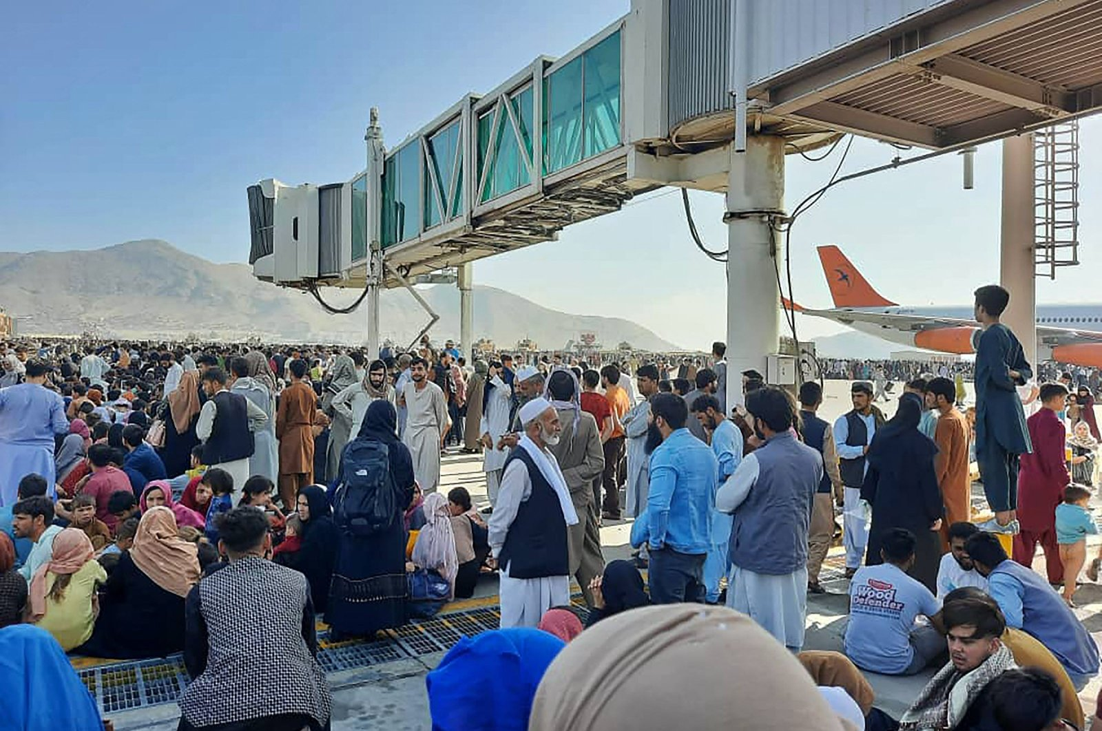 Afghans crowd the tarmac of the Kabul airport to flee the country as the Taliban take control of Afghanistan after President Ashraf Ghani fled the country and conceded the insurgents had won the 20-year war, Kabul, Afghanistan, Aug. 16, 2021. (AFP File Photo)
