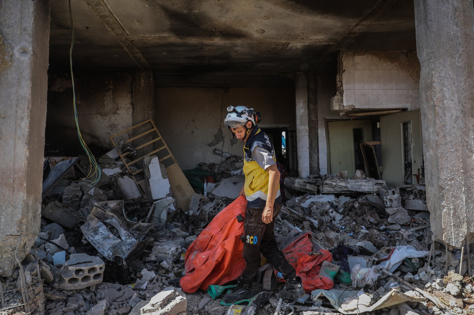 A member of the White Helmets inspects the damage at the group's center after it was targeted by warplanes in Idlib, Syria. (Getty Images)