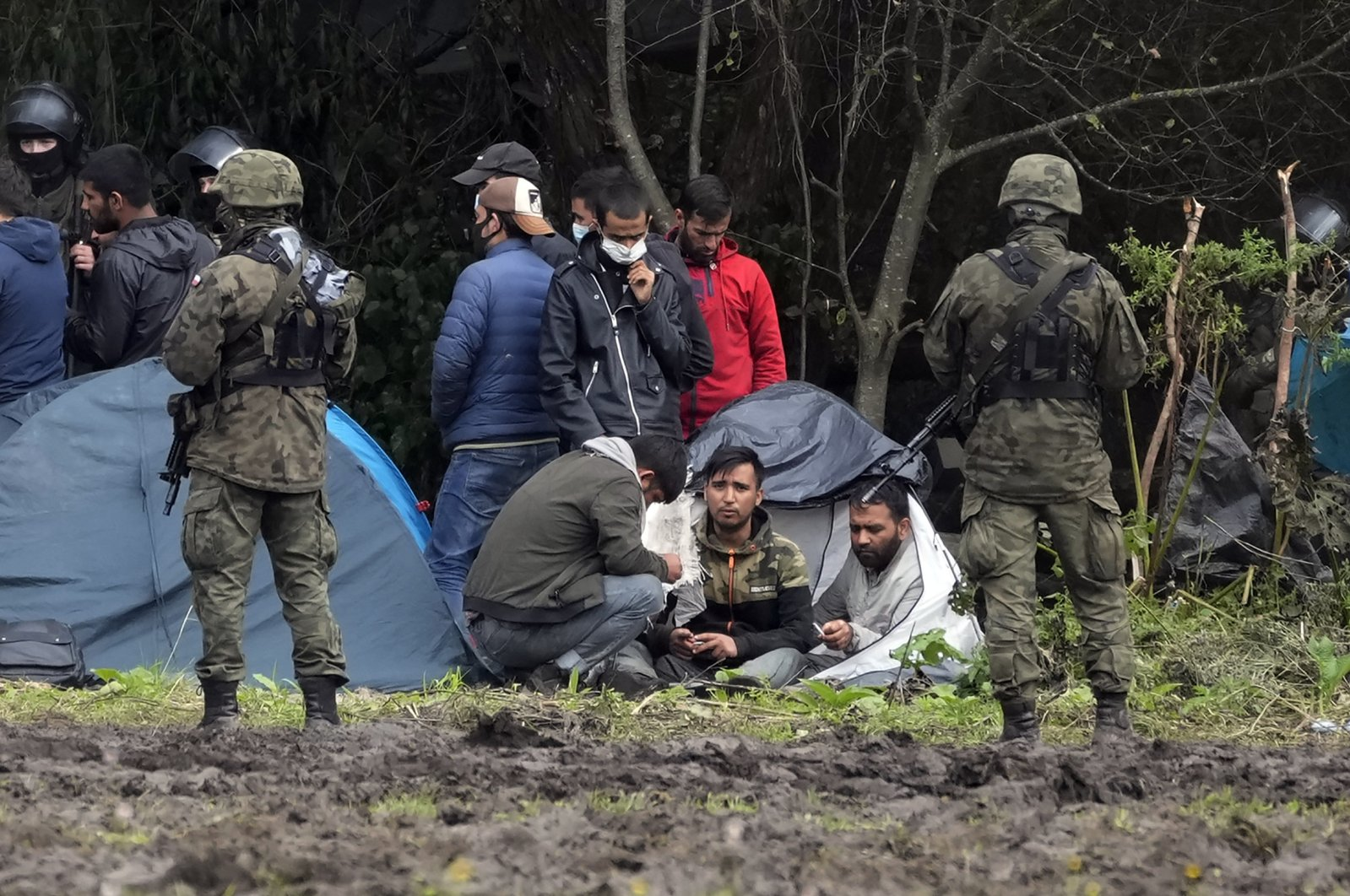 Polish security forces surround migrants stuck along with border with Belarus in Usnarz Gorny, Poland, Sept. 1, 2021. (AP Photo)