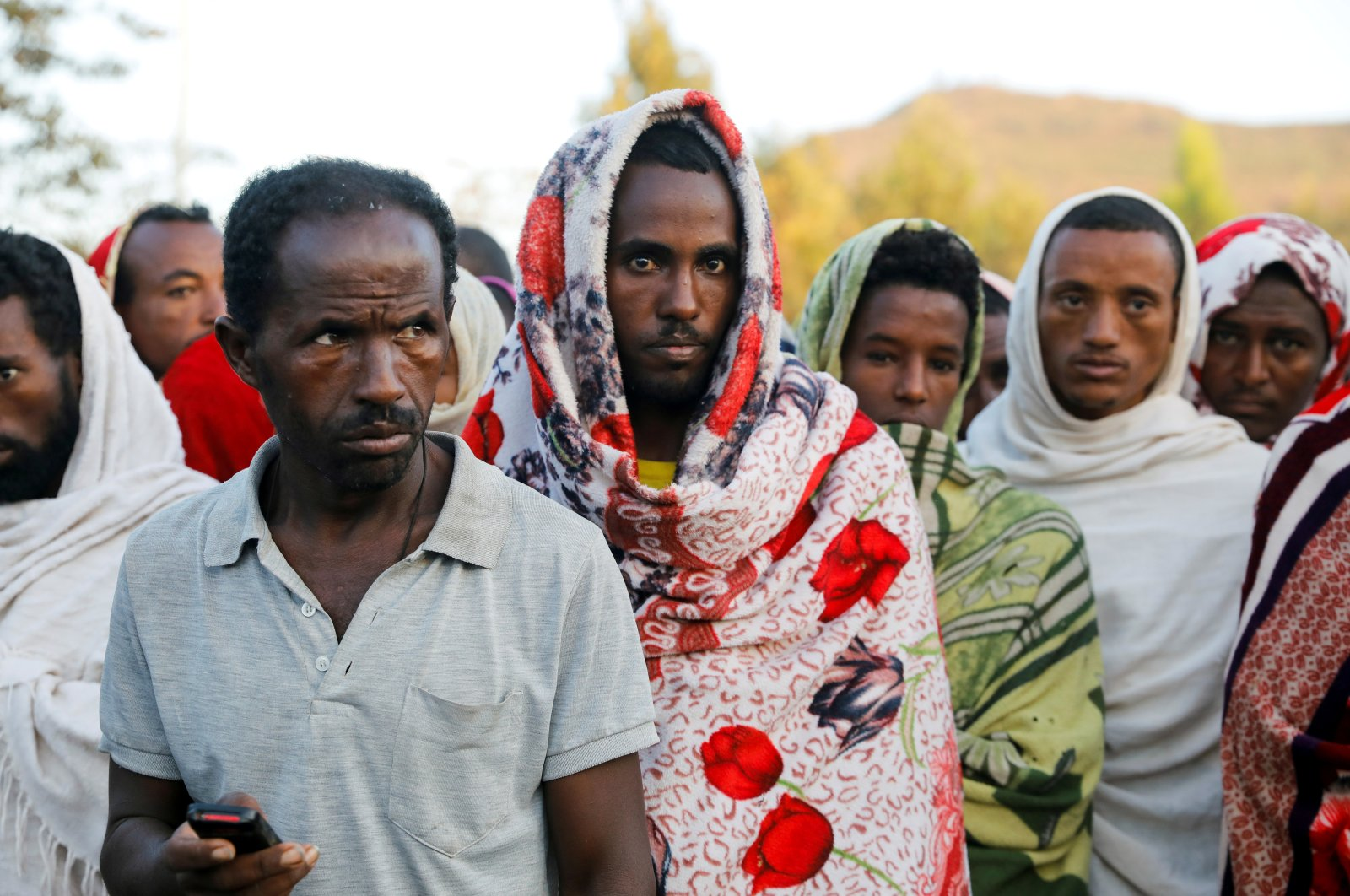 Men stand in line to receive food donations, at the Tsehaye primary school, which was turned into a temporary shelter for people displaced by conflict, in the town of Shire, Tigray region, Ethiopia, March 15, 2021. (Reuters Photo)
