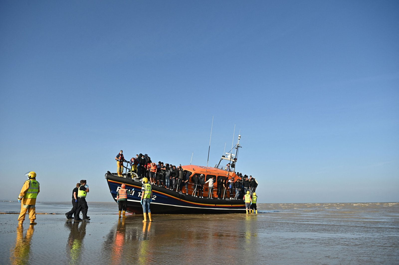 Migrants stand aboard an RNLI (Royal National Lifeboat Institution) lifeboat after being rescued crossing the English Channel at a beach in Dungeness, southeast England, Sept. 7, 2021. (AFP Photo)