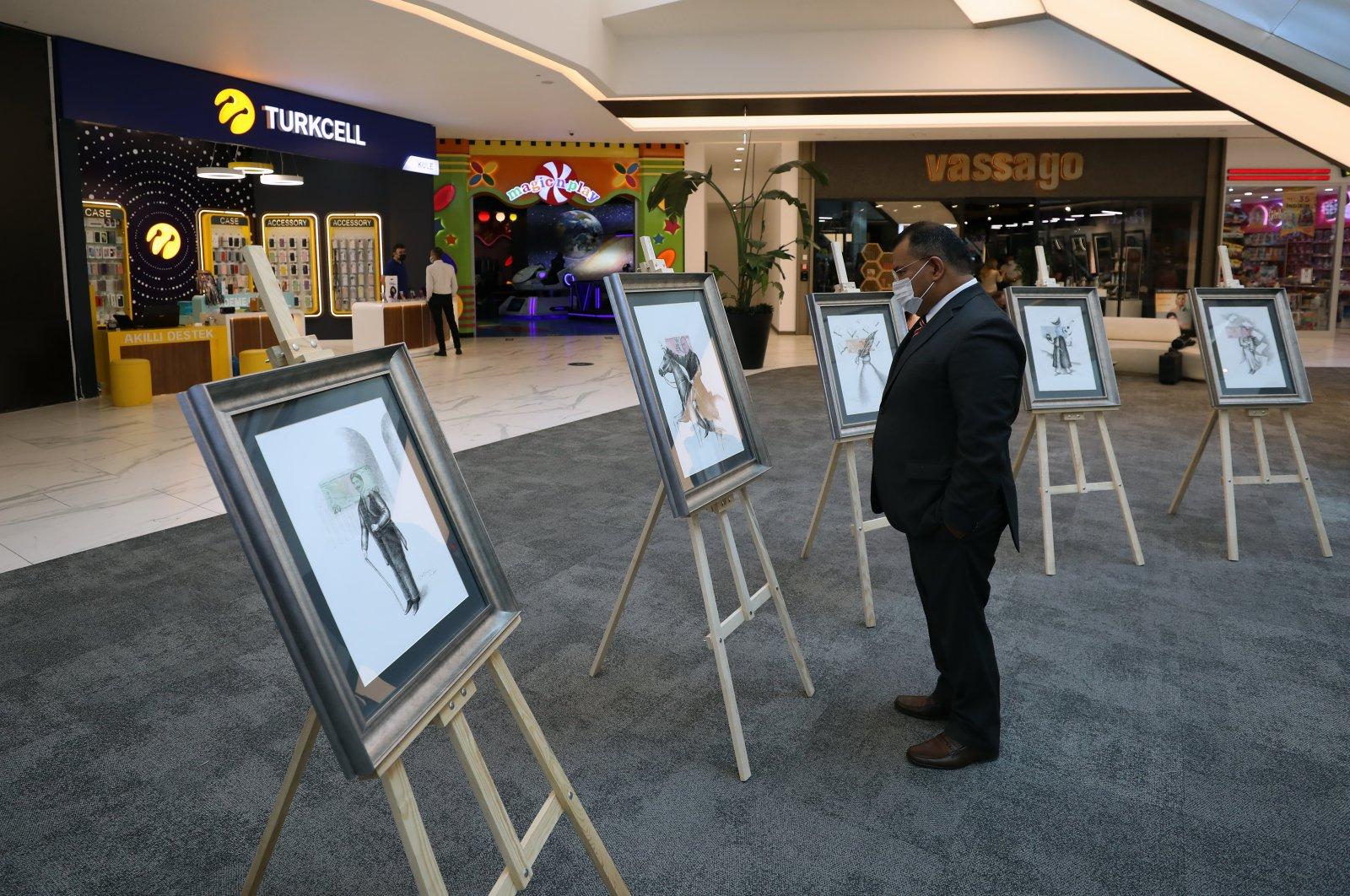 A visitor examines works by Fernando Valdiviezo at the exhibition, Ankara, Turkey, Sept. 8, 2021. (AA Photo)