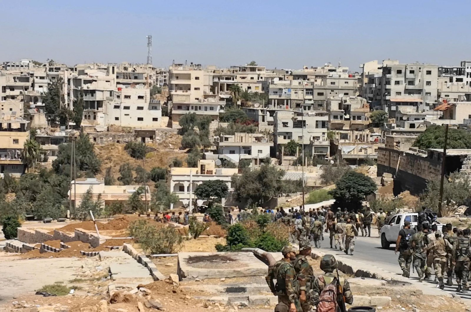 A handout picture released by the regime-linked Syrian Arab News Agency (SANA) on Sept. 8, 2021, shows the Assad regime army entering the opposition-held Daraa al-Balad district of Daraa city under a cease-fire deal brokered by the government's ally Russia. (Photo by SANA via AFP)