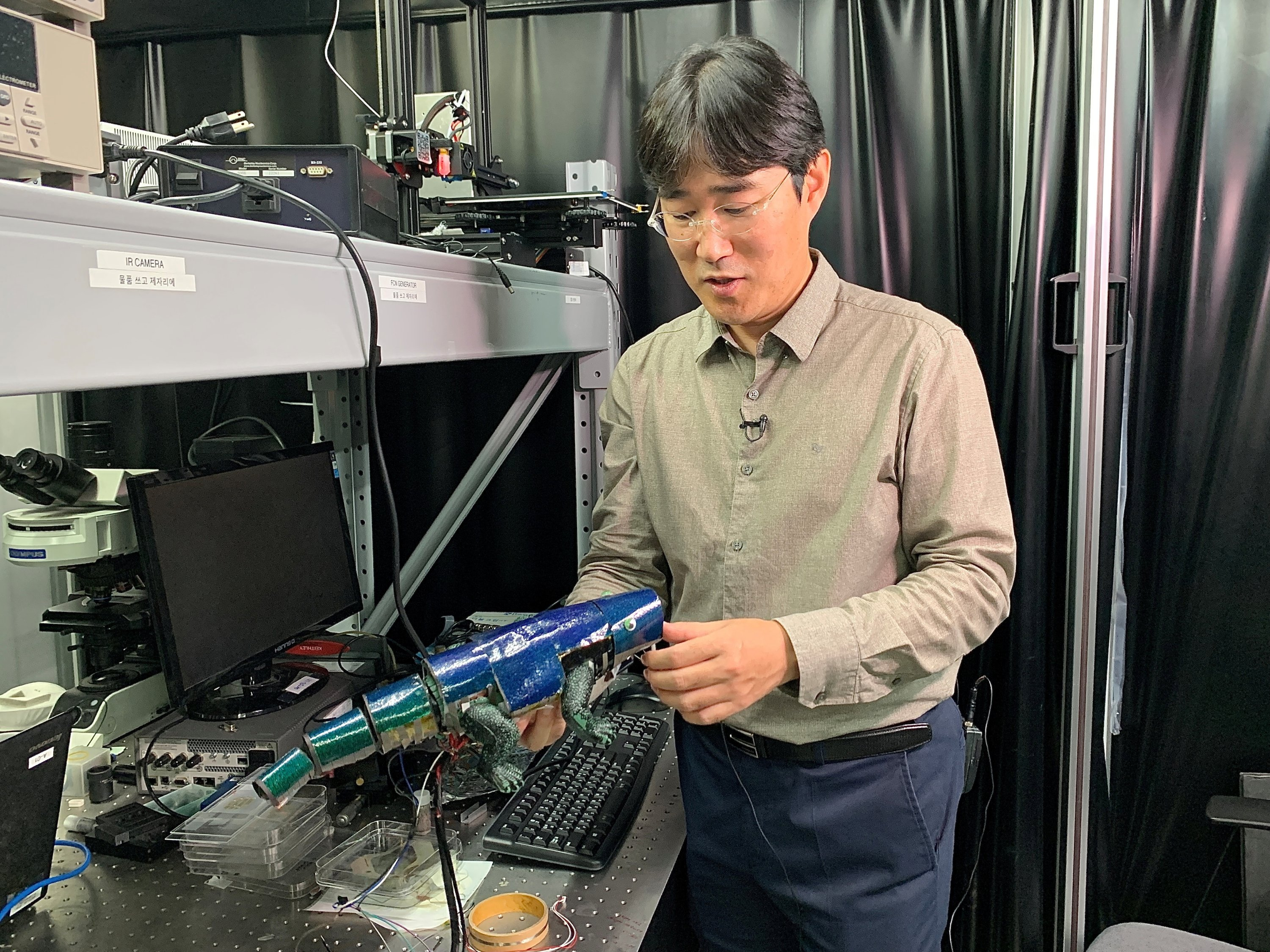 Ko Seung-hwan, a mechanical engineering professor at Seoul National University, looks at a chameleon robot covered with artificial skin, in Seoul, South Korea, Sept. 7, 2021. (Reuters Photo)