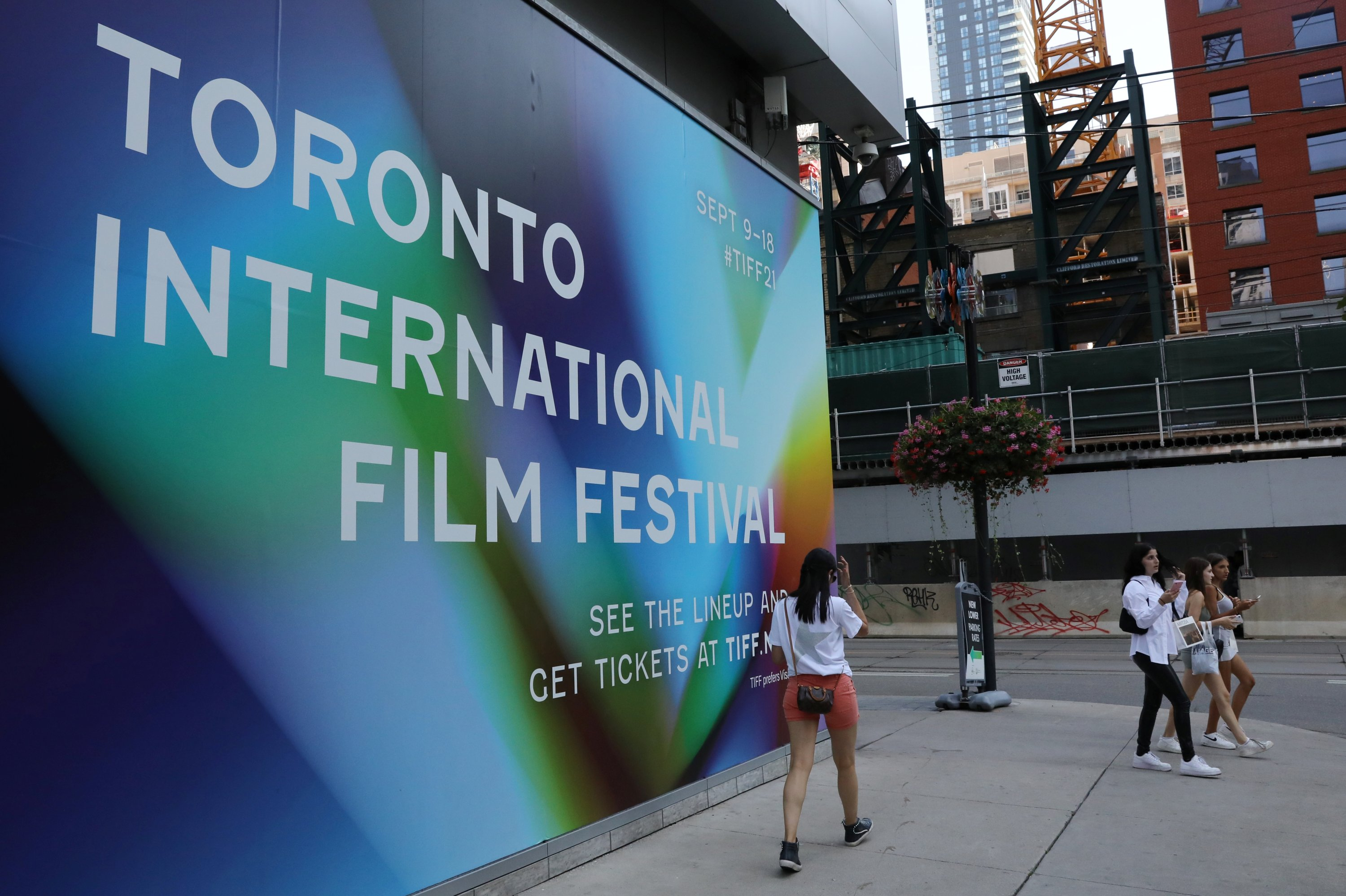 People pass a large mural on the Bell Lightbox headquarters of the Toronto International Film Festival (TIFF) in Toronto, Ontario, Canada September 7, 2021.  (REUTERS Photo)
