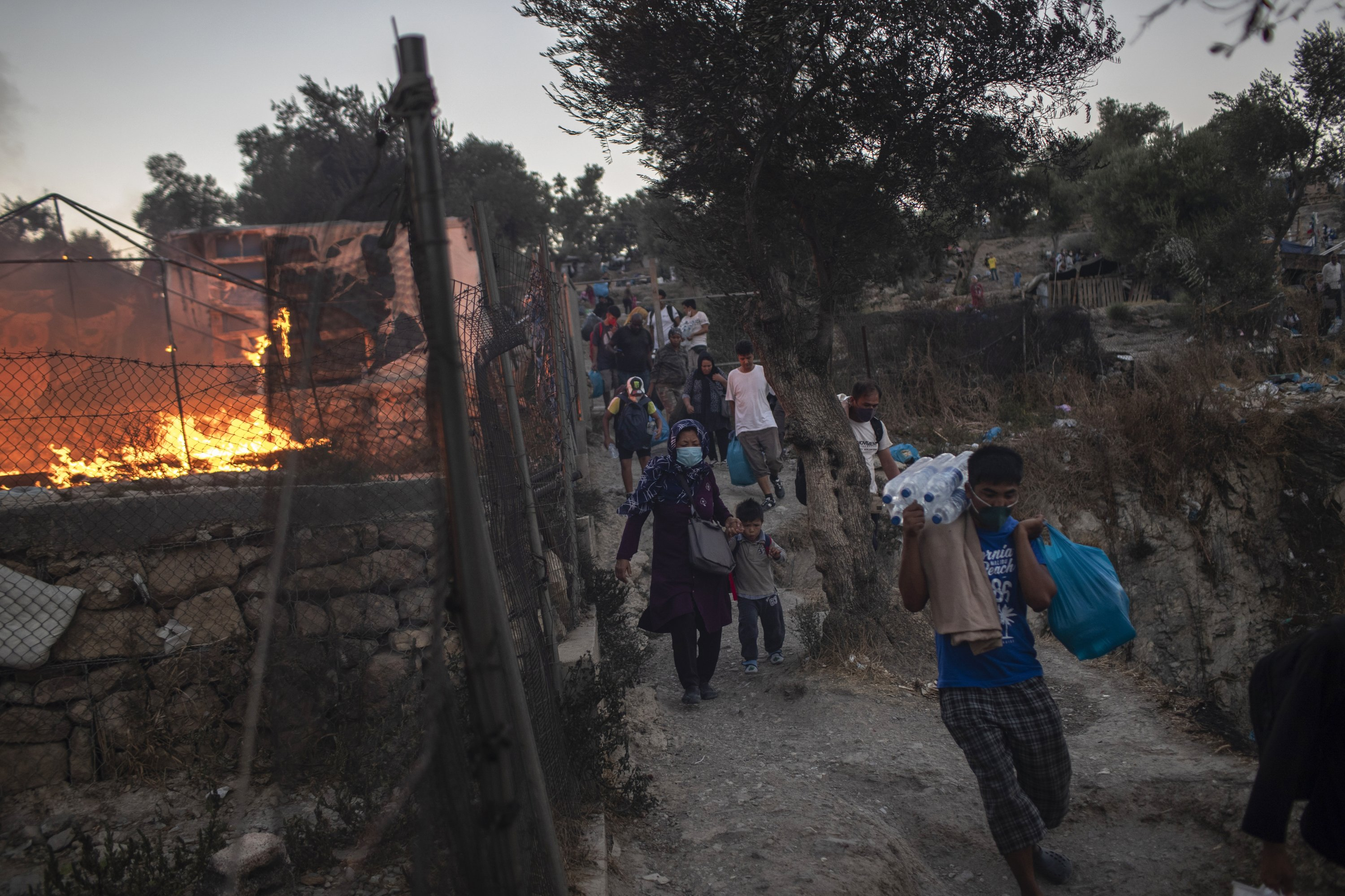 Refugees and migrants carrying their belongings flee a fire burning at Moria camp, on Lesbos island, Greece, Sept. 9, 2020. (AP Photo)