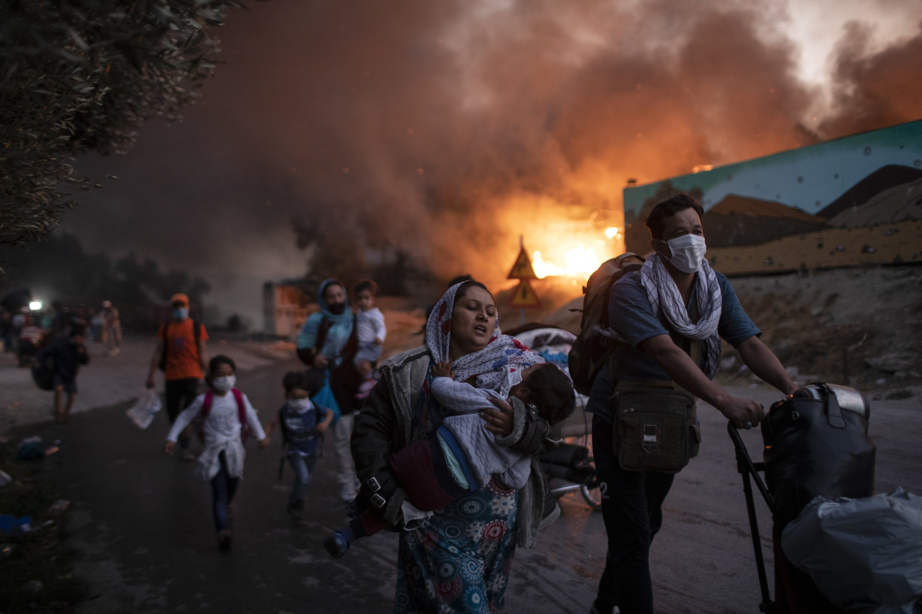 Refugees and migrants carrying their belongings flee a fire burning at the Moria camp on the northeastern Aegean island of Lesbos, Greece, Sept. 9, 2020. (AP Photo)