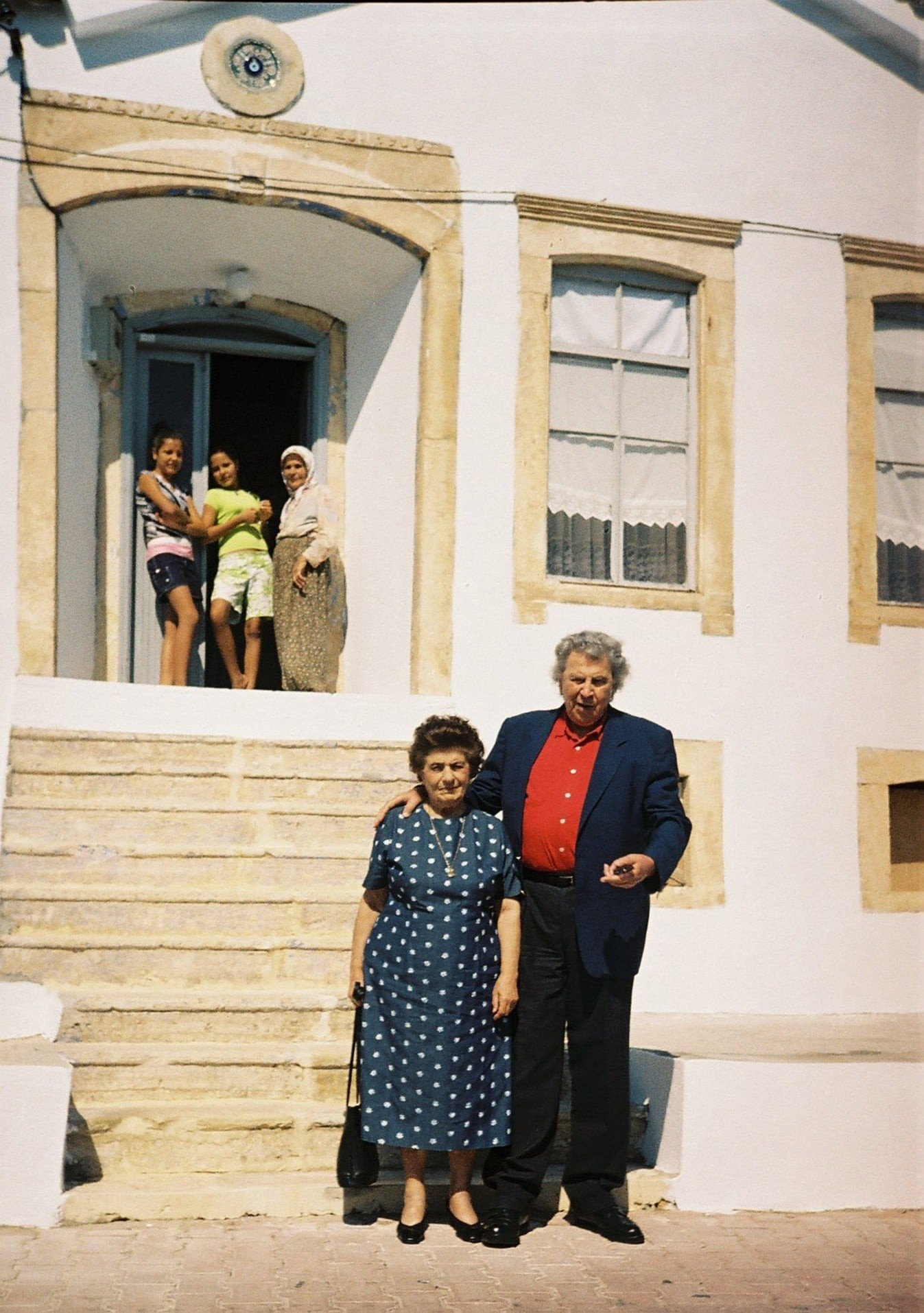 This file photo provided on Sept. 3, 2021, shows Mikis Theodorakis and his wife posing in front of his mother's former house in Çeşme, western Turkey. (IHA Photo)