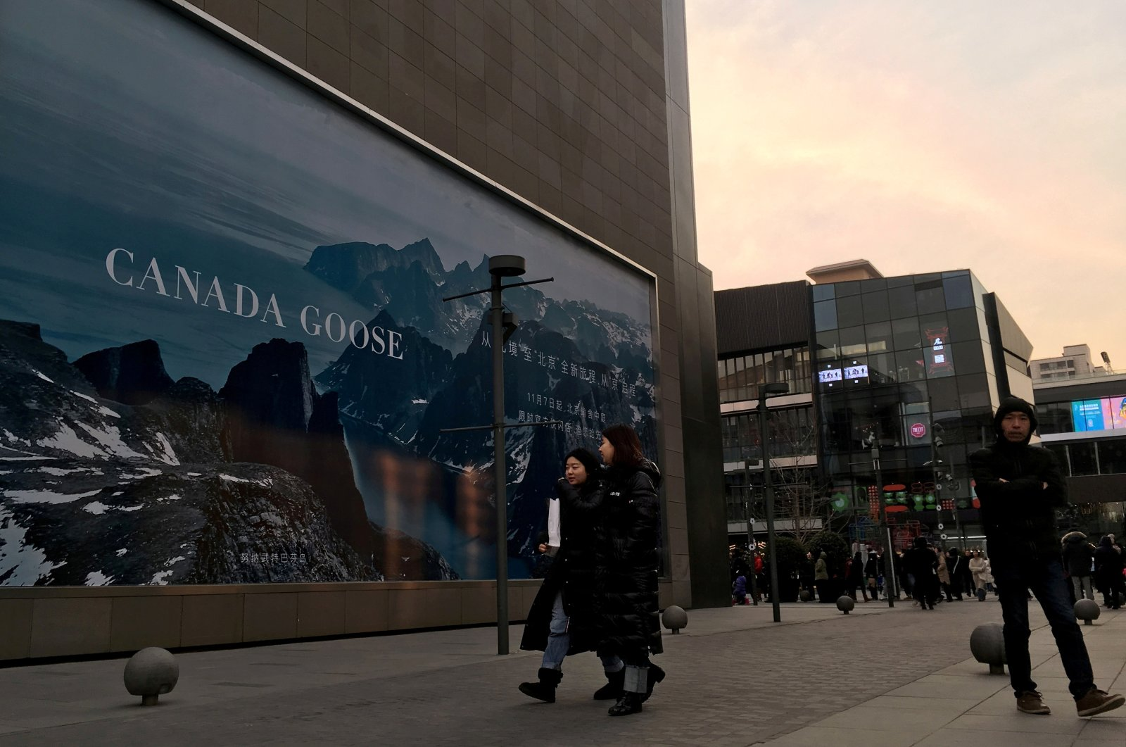 People walk past an advertisement near the flagship store of Canadian luxury parka maker Canada Goose in Sanlitun, Beijing, China, Dec. 31, 2018. (Reuters Photo)