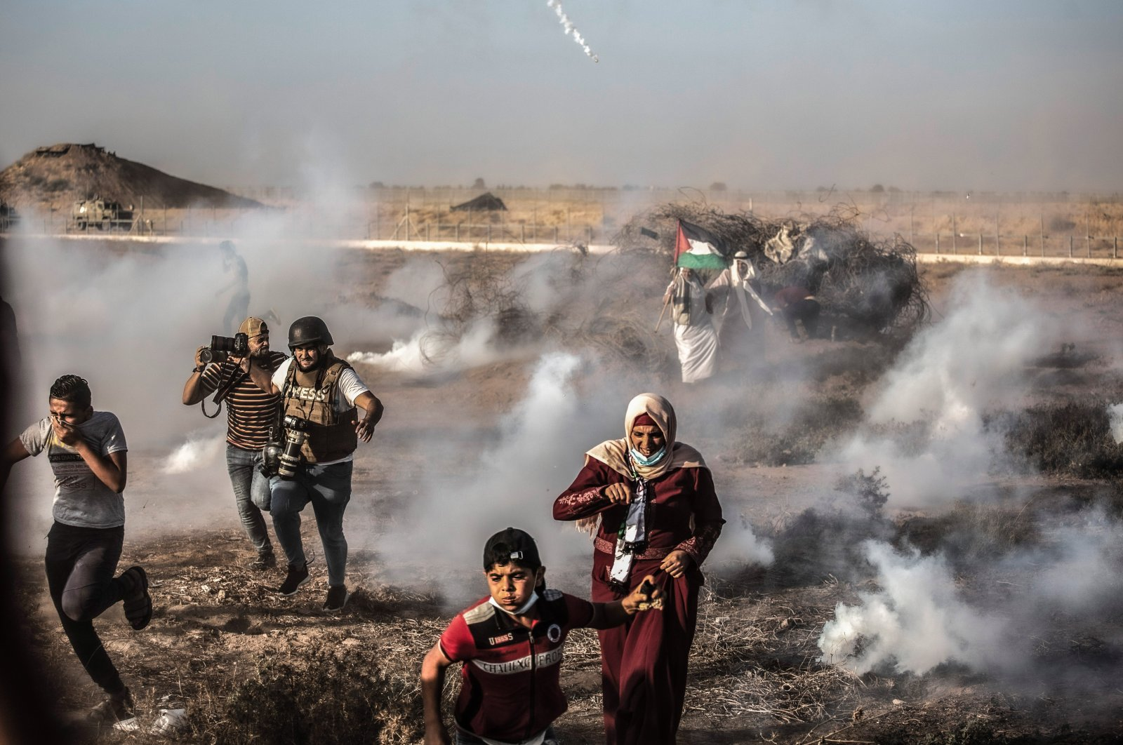 Palestinian demonstrators flee tear gas fired by Israeli forces during the demonstration near the border between Israel and the Gaza Strip, Palestine, Aug. 25, 2021. (Photo by Getty Images)