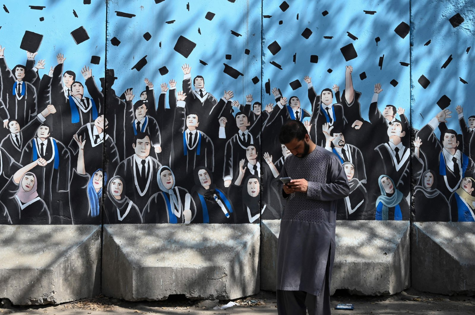 A man uses his mobile phone in front of a mural outside Afghanistan's Ministry of Higher Education, Kabul, Afghanistan, Sept. 9, 2021. (AFP Photo)