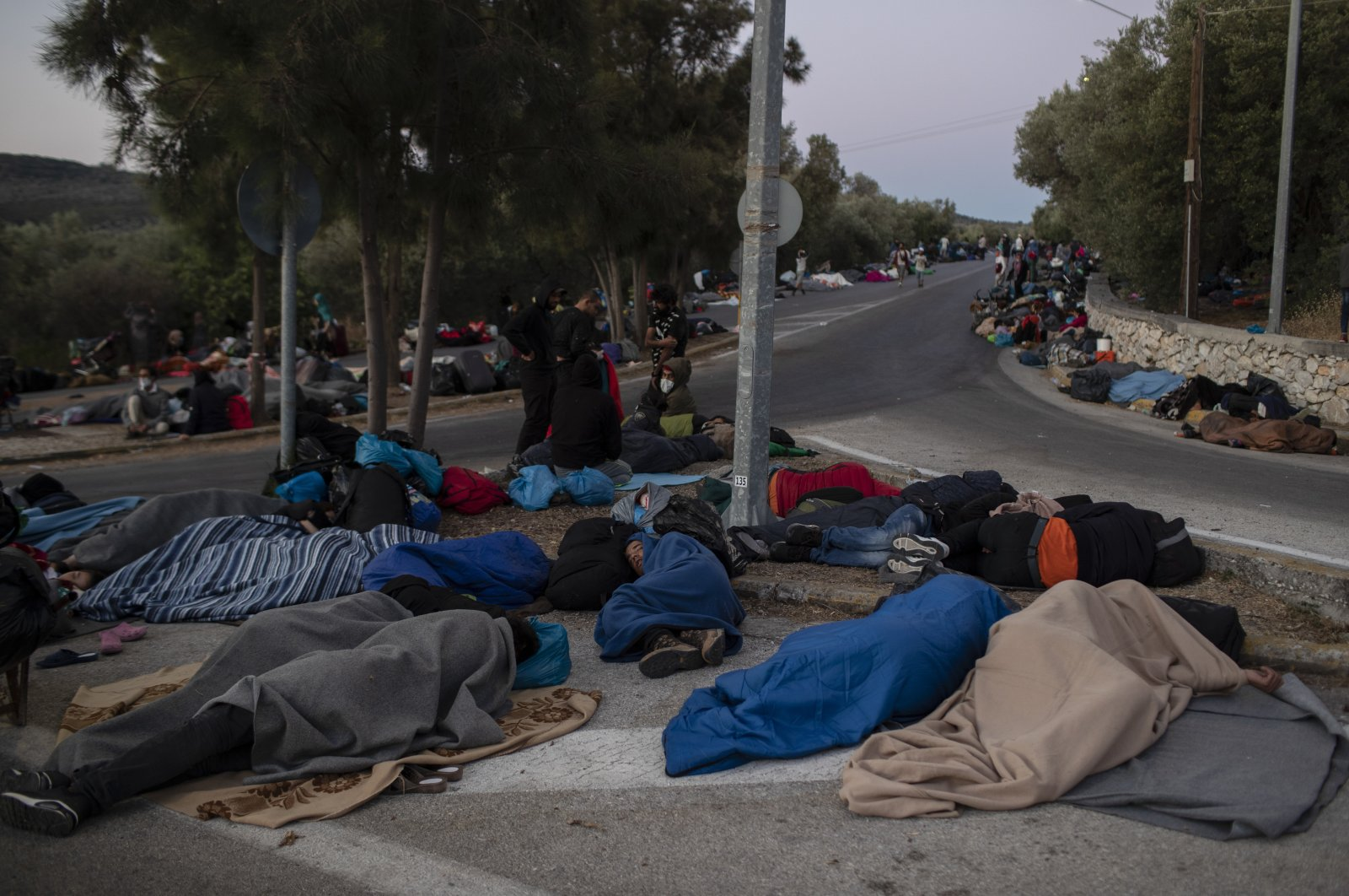 Refugees and migrants sleep on a street near the destroyed Moria camp following a fire, on Lesbos island, Greece, Sept. 10, 2020. (AP Photo)