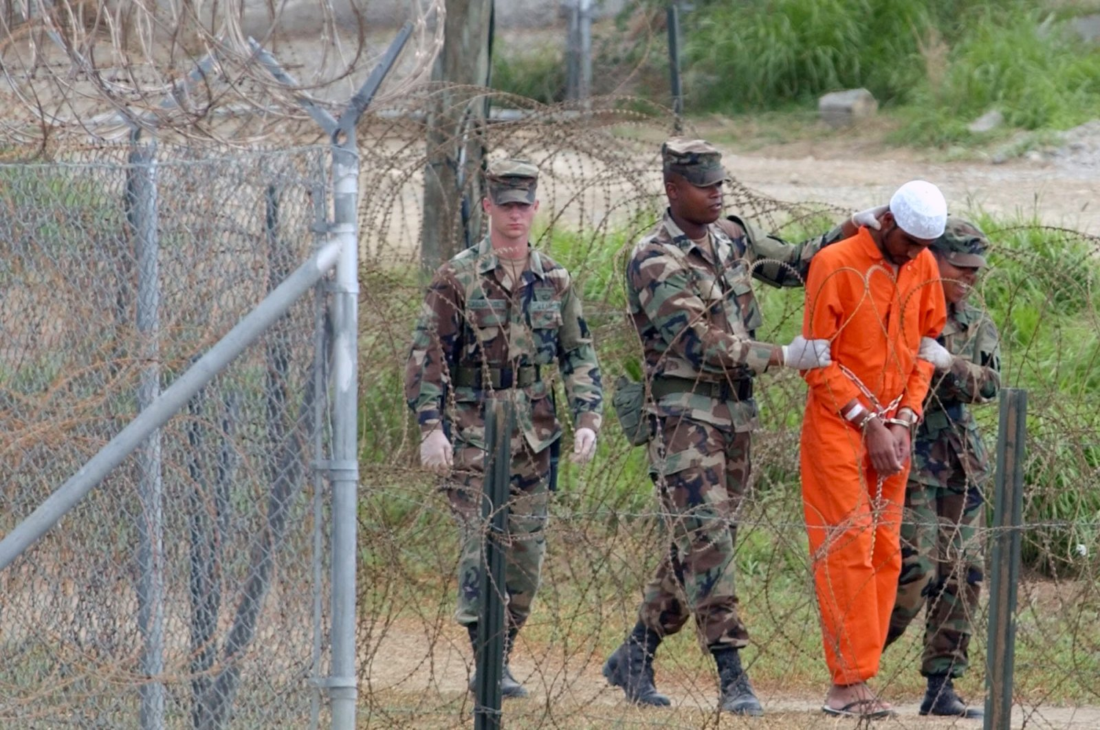 In this Feb. 6, 2002, file photo a detainee is led by military police to be interrogated by military officials at Camp X-Ray at the U.S. Naval Base at Guantanamo Bay, Cuba. (AP Photo)