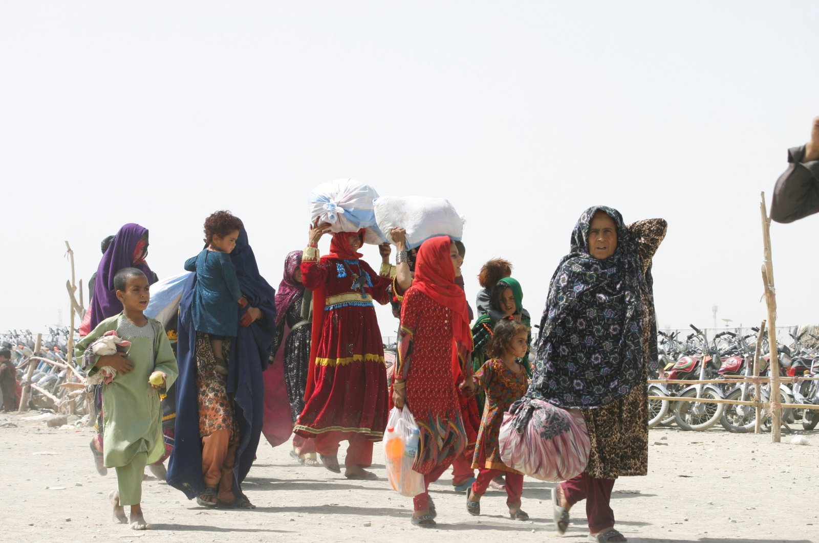 """People from Afghanistan walk with their belongings as they cross into Pakistan at the """"Friendship Gate"""" crossing point, in the Pakistan-Afghanistan border town of Chaman, Pakistan, Sept. 7, 2021. (Reuters Photo)"""