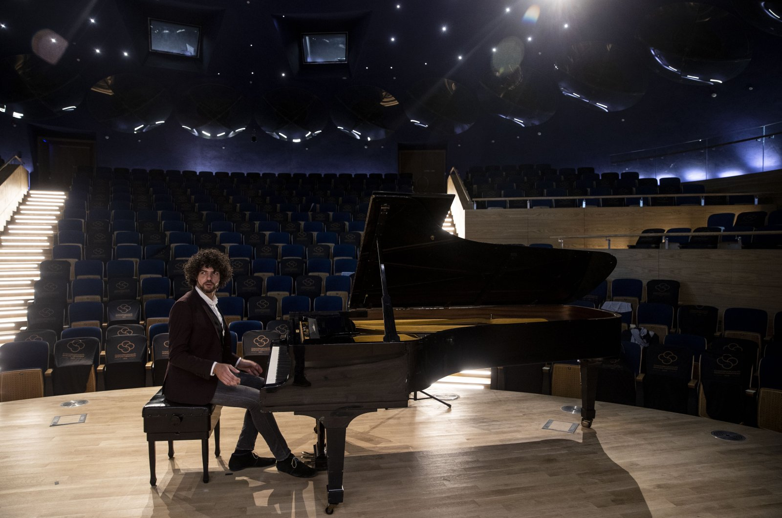 French pianist Simon Ghraichy poses with a piano at the Presidential Symphony Orchestra's concert hall, Ankara, Turkey, Sept. 8, 2021. (AA Photo)