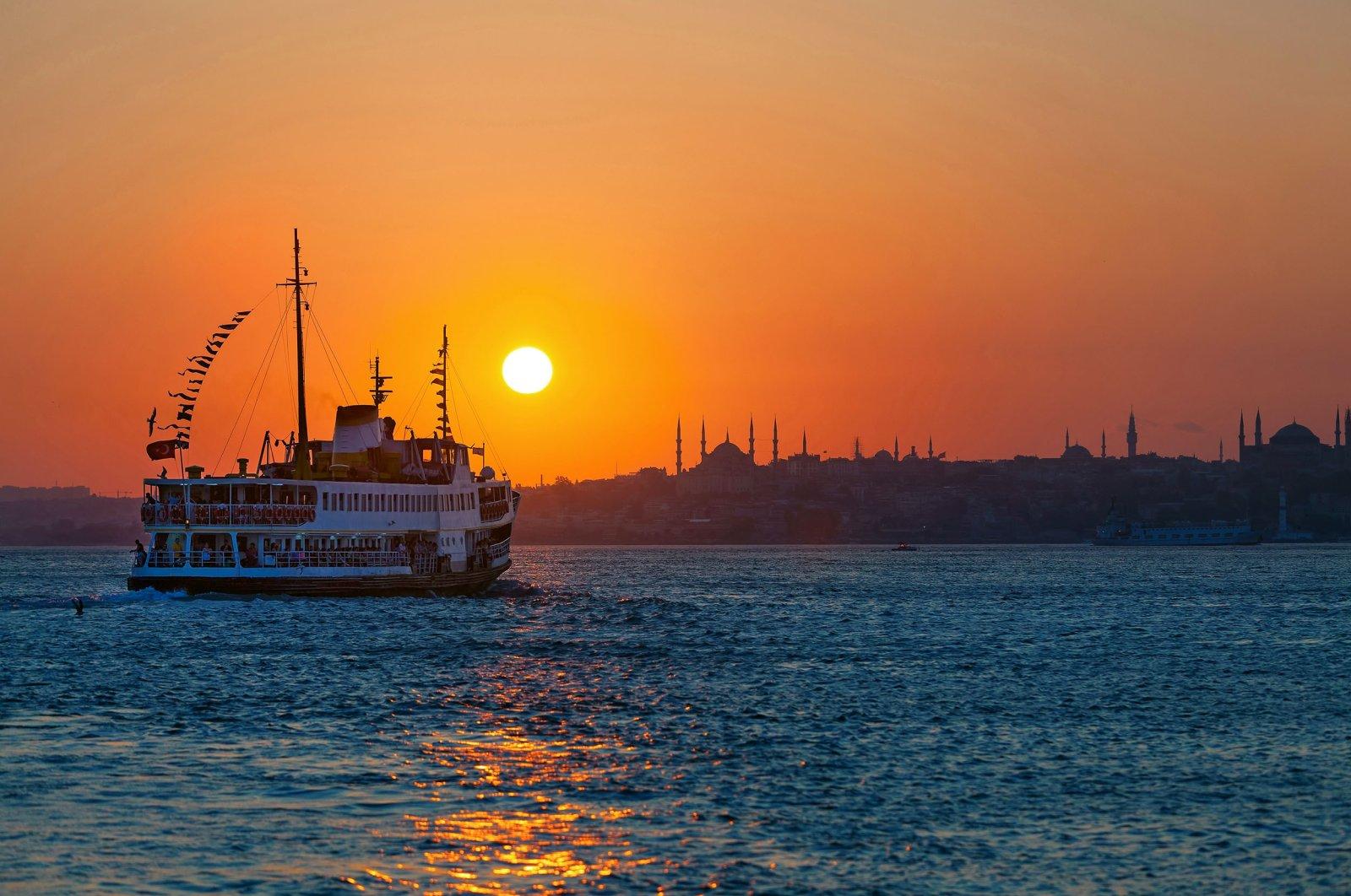 Passenger ferry floats across the Bosporus at sunset, Istanbul, Turkey. (Shutterstock Photo)