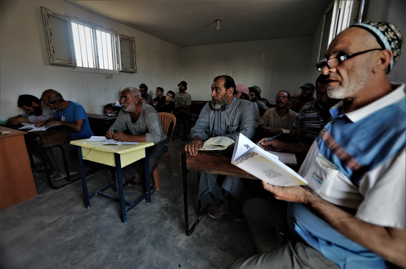 Adults attend a literacy class at a course run by the local council in al-Bab, northern Syria, Sept. 8, 2021. (AA Photo)
