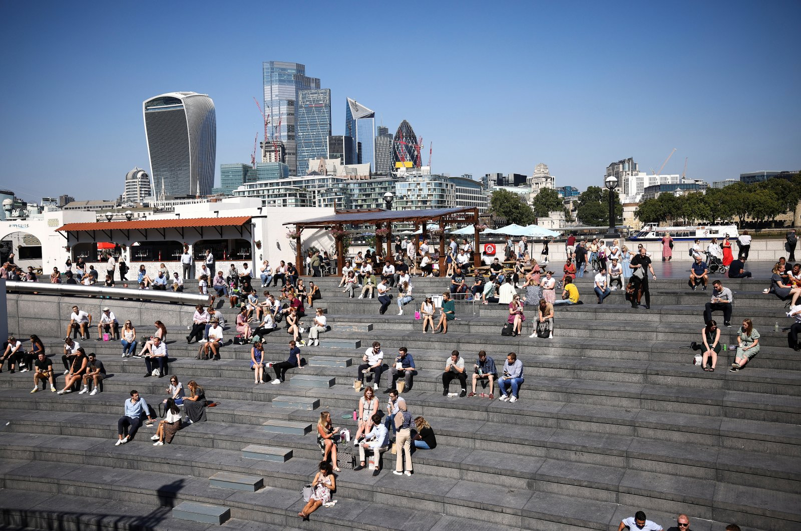 London's financial district can be seen in the background as people relax in the sunny weather on the south side of the River Thames in London, Britain, Sept. 7, 2021. (Reuters Photo)