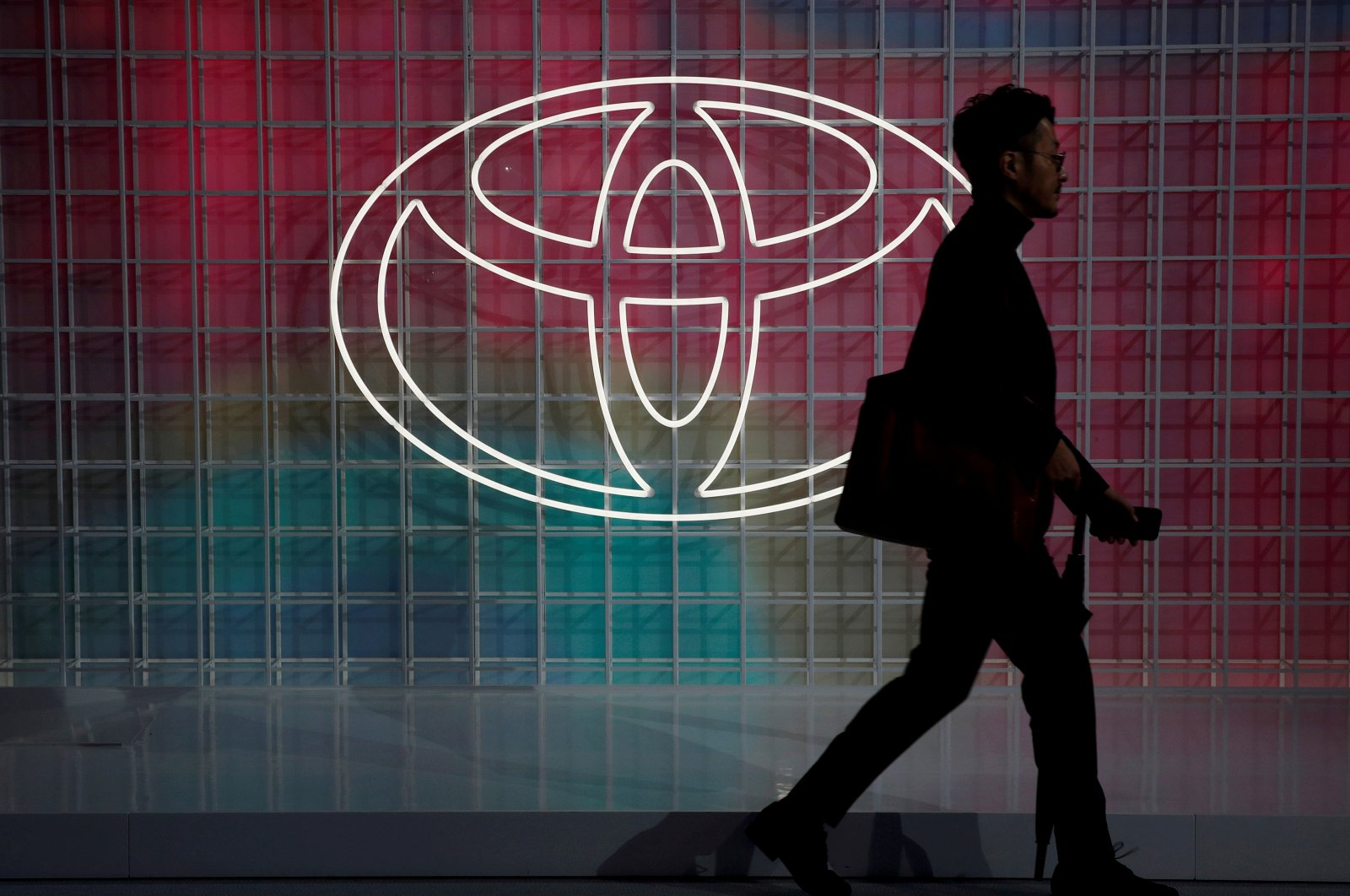 A man walks past a Toyota logo at the Tokyo Motor Show, in Tokyo, Japan, Oct. 24, 2019. (Reuters Photo)