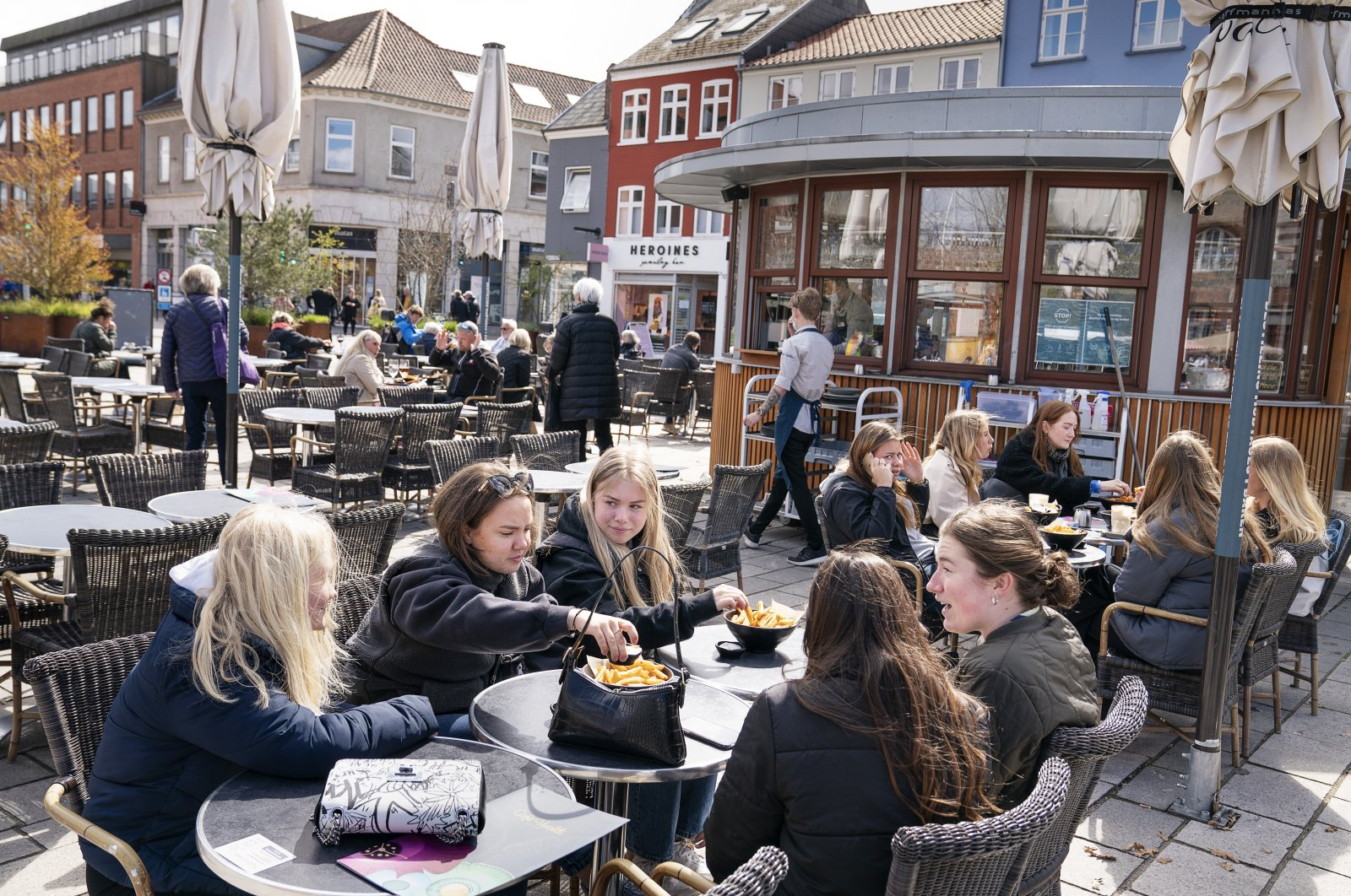 People sit outside a restaurant as cafes and bars are reopened, in Roskilde, Denmark, April 21, 2021. (AP Photo)