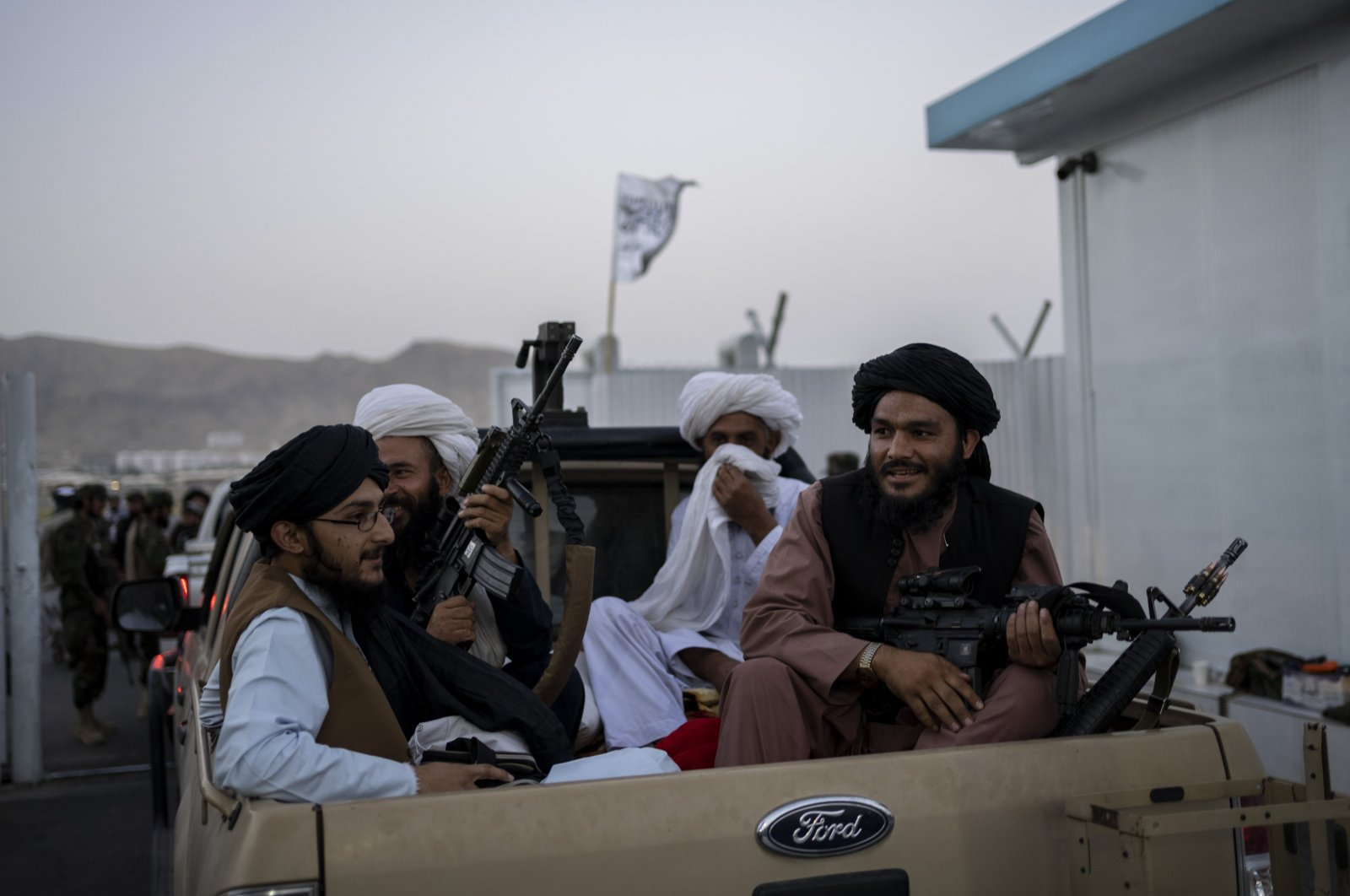Taliban fighters sit in a pickup truck at the airport in Kabul, Afghanistan, Sept. 9, 2021. (AP Photo)