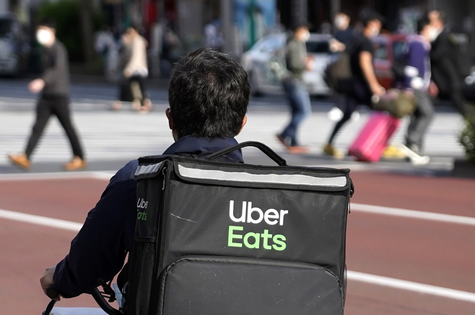 An Uber Eats delivery person rides a bicycle through the Shinjuku district in Tokyo, Japan, April 28, 2021. (AP File Photo)