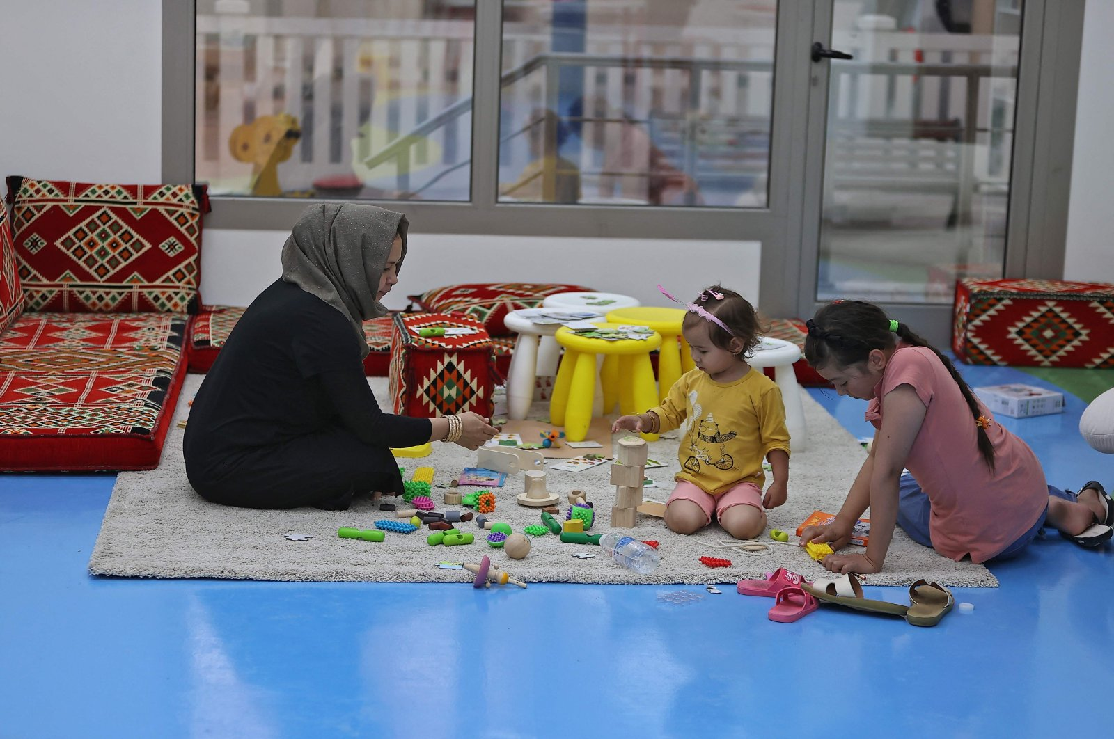 Afghan refugee children play at an indoor space near their accommodation at Park View Villas, a Qatar's 2022 FIFA World Cup residence designated to host the event's organizing committee, transformed into a housing center for Afghan refugees, in Doha, Qatar, Sept. 2, 2021. (AFP Photo)