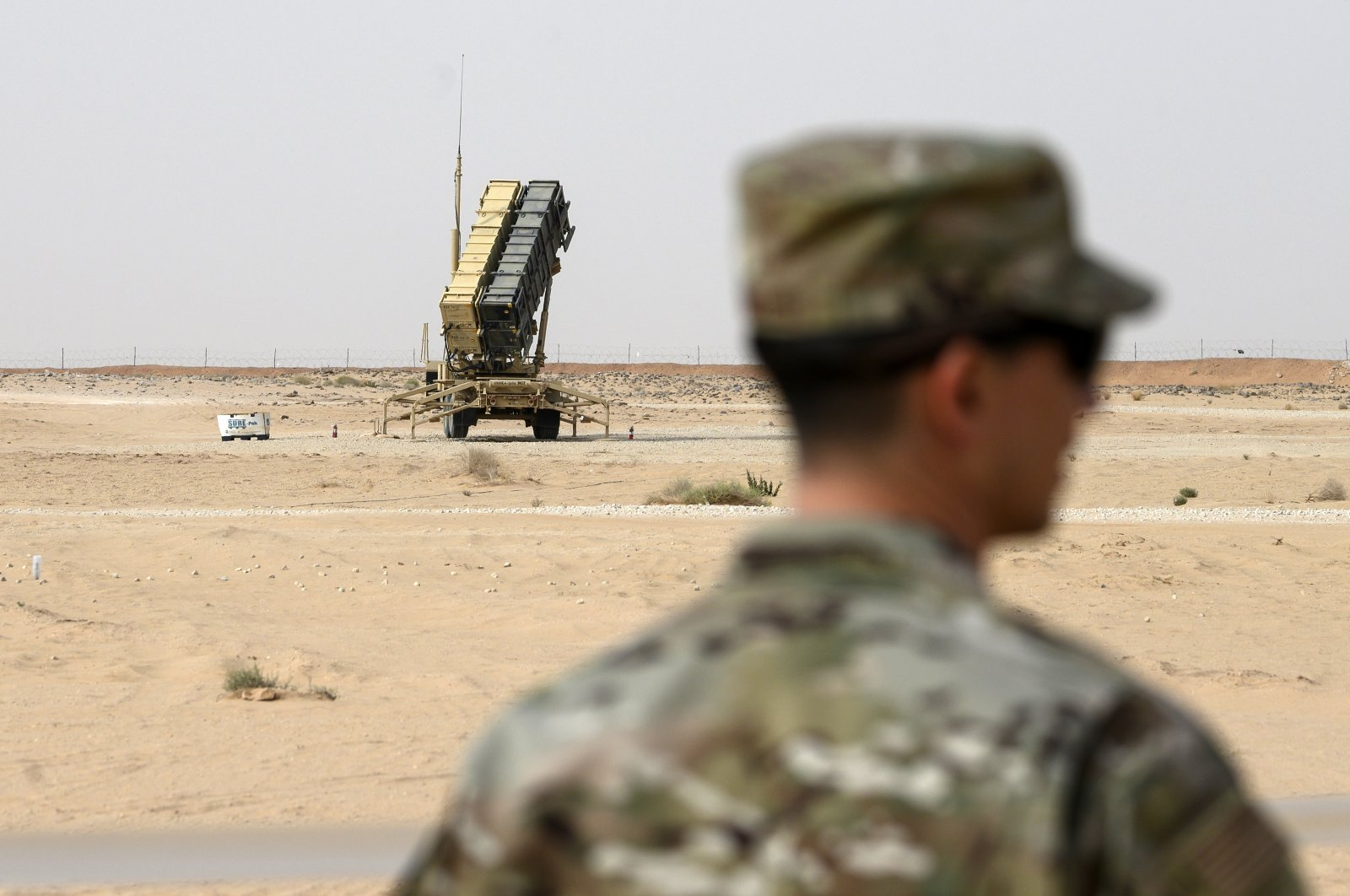A member of the U.S. Air Force stands near a Patriot missile battery at Prince Sultan Air Base in Saudi Arabia, Feb. 20, 2020. (Pool via AP)