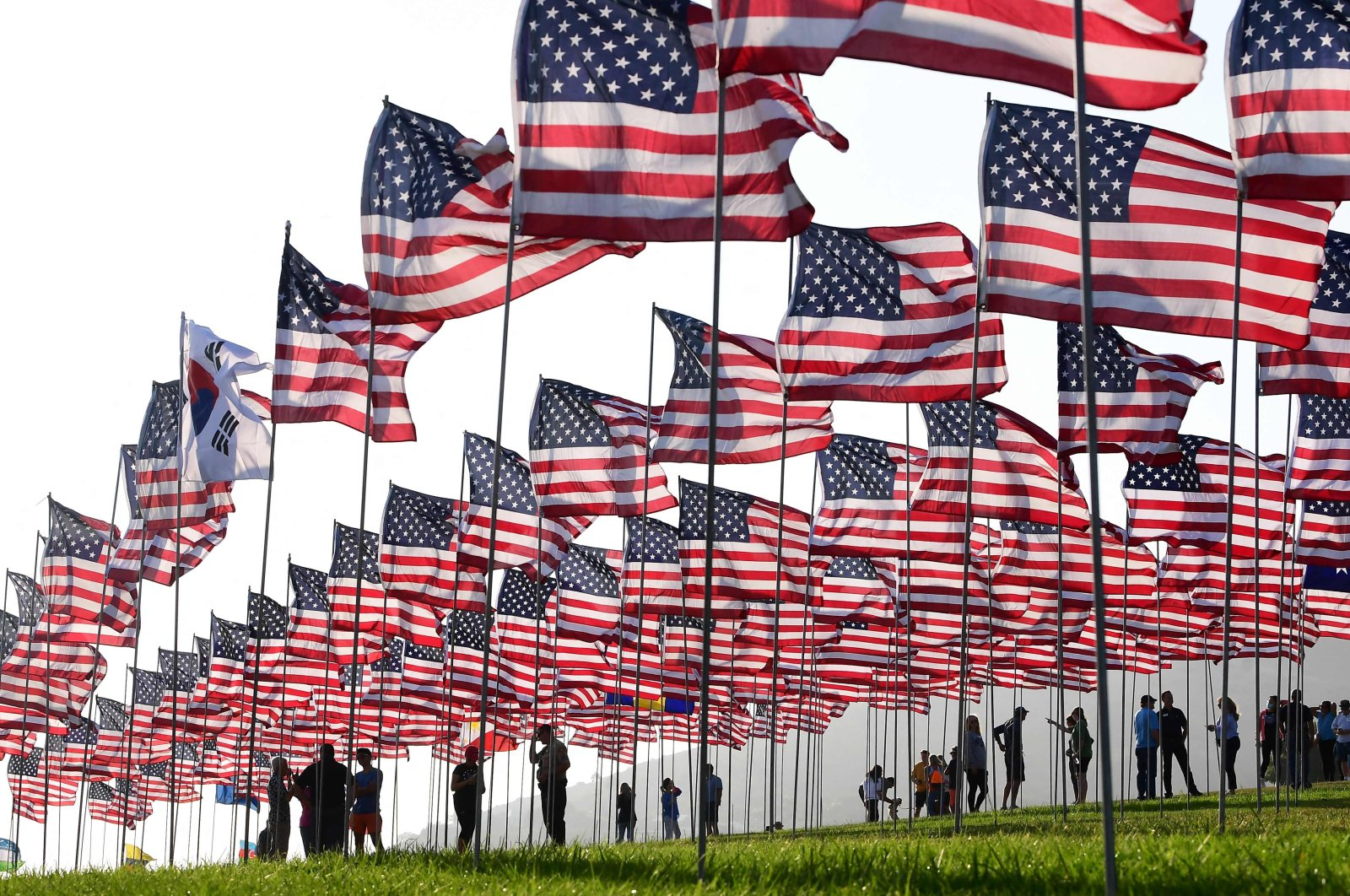 People help with the display of U.S. flags to commemorate the 20th anniversary of 9/11 with the annual Waves of Flags display and remembrance at Pepperdine University in Malibu, California, U.S., Sept. 8, 2021. (AFP Photo)
