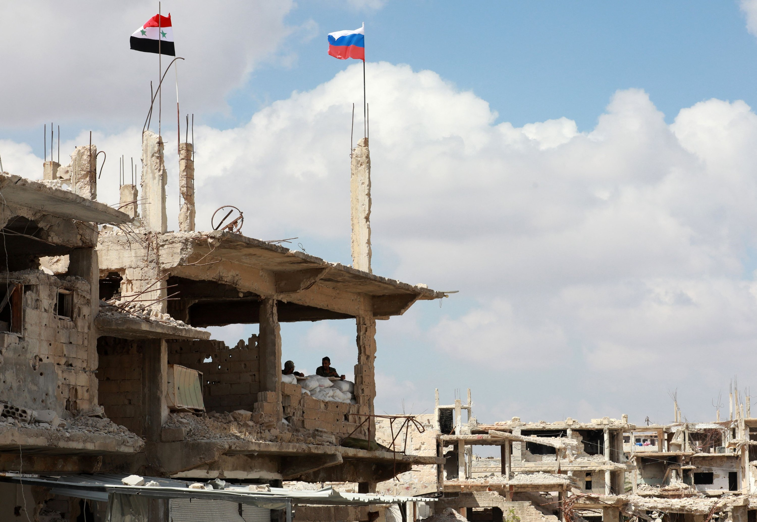 A Syrian and a Russian flag fly above a damaged building in the district of Daraa al-Balad of Syria's southern city of Daraa, on Sept. 12, 2021. (AFP Photo)