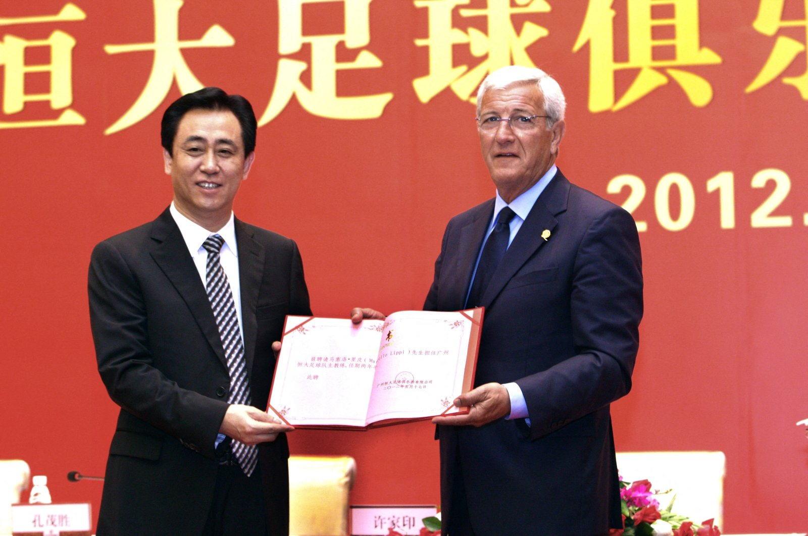 Chairperson of Guangzhou Evergrande, Xu Jiayin (L), posing with World Cup-winning football coach Marcello Lippi during a signing ceremony in Guangzhou, Guangdong province, southern China, May 17, 2012. (AFP Photo)