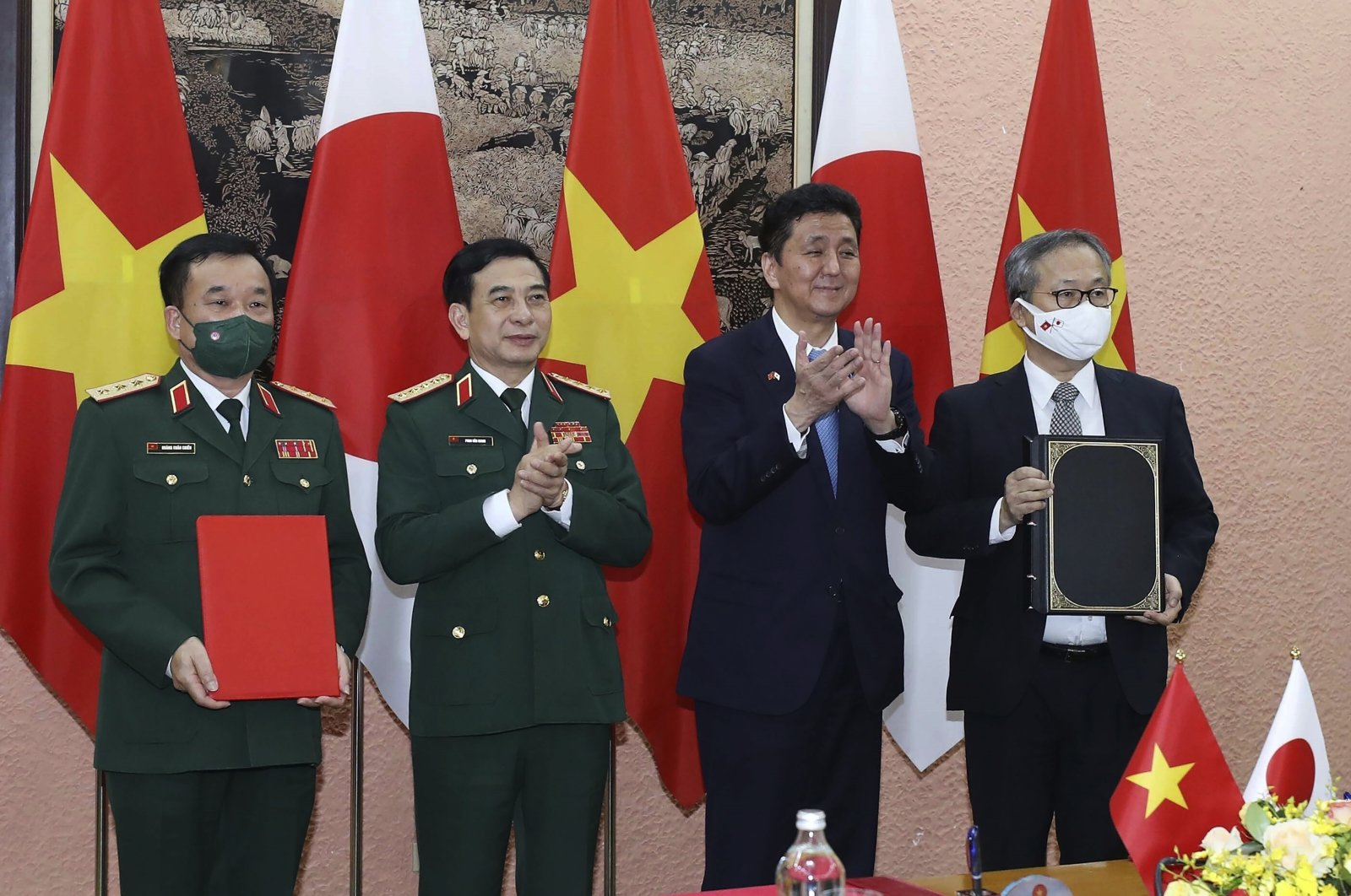 Vietnamese Defense Minister Phan Van Giang, center left, and Japanese Defense Minister Nobuo Kishi, center right, stand for photo with their officials after signing an agreement in Hanoi, Vietnam, Sept. 12, 2021. (AP Photo)