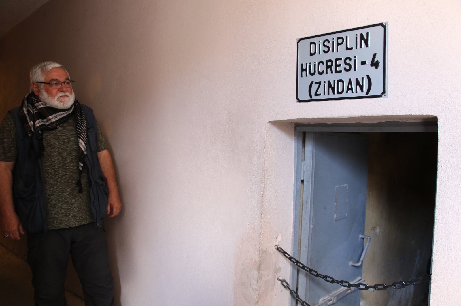 """Mahir Damatlar, a victim of the 1980 coup, looks at a """"disciplinary cell"""" for people imprisoned by the junta at Ulucanlar prison, in the capital Ankara, Turkey, Sept. 12, 2021. (IHA PHOTO)"""
