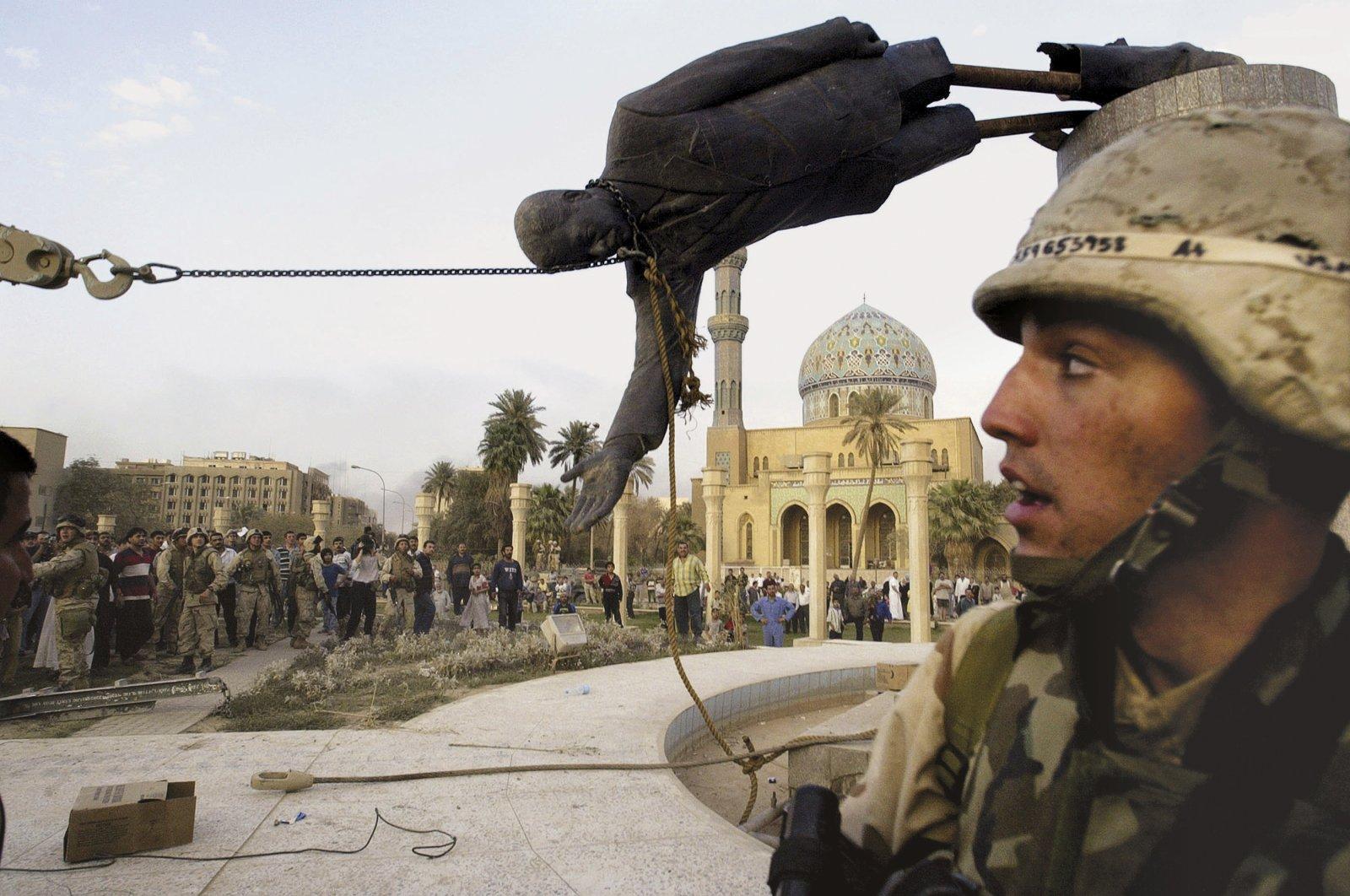 Iraqi civilians and U.S. soldiers pull down a statue of Saddam Hussein in downtown Baghdad, Iraq, April 9, 2003. (AP Photo)