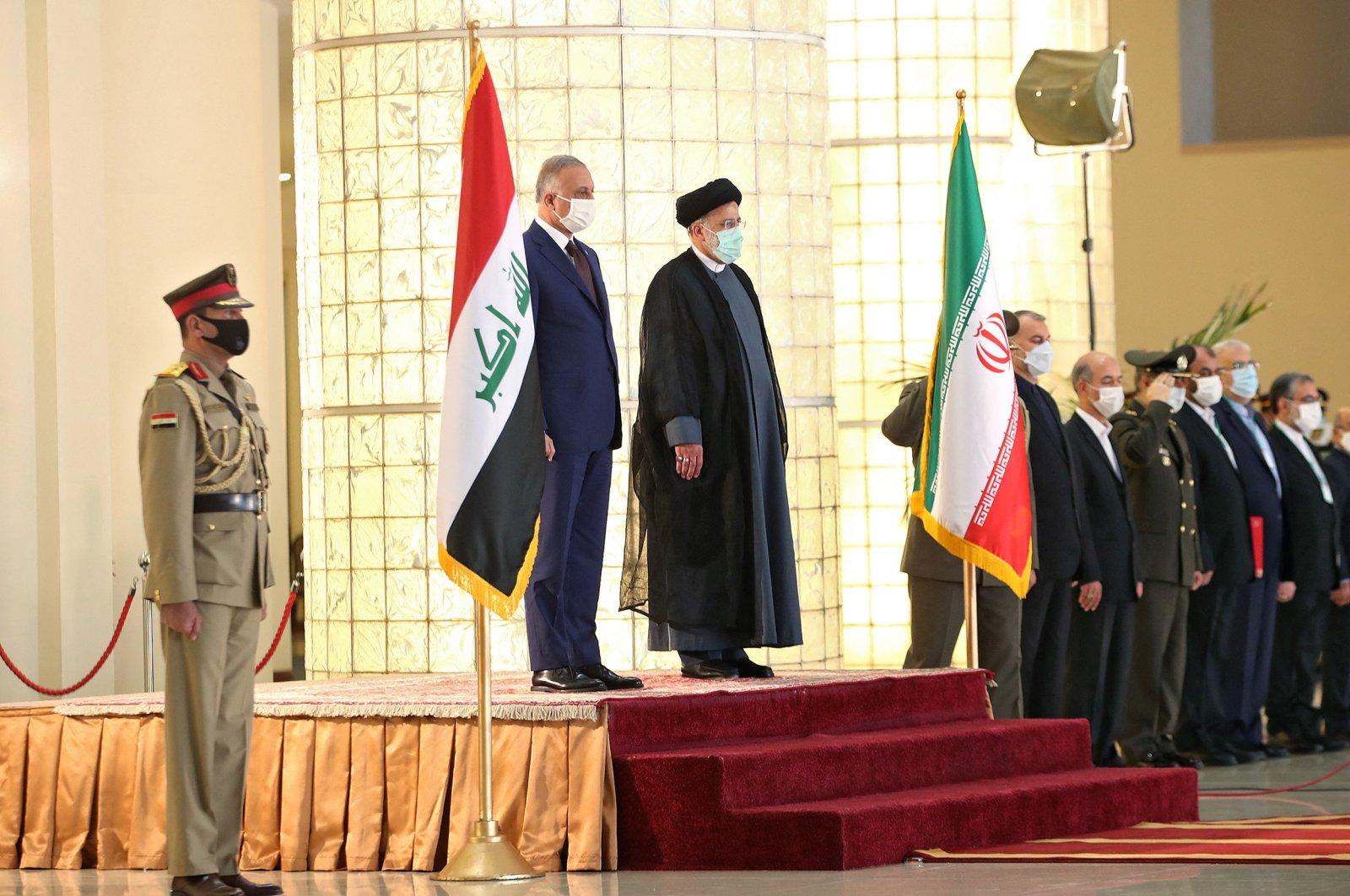 A handout picture provided by the Iranian presidency on September 12, 2021, shows President Ebrahim Raisi (C) receiving Iraqi Prime Minister Mustafa Al-Kadhemi (L) in the capital Tehran. (AFP Photo/HO/Iranian Presidency)