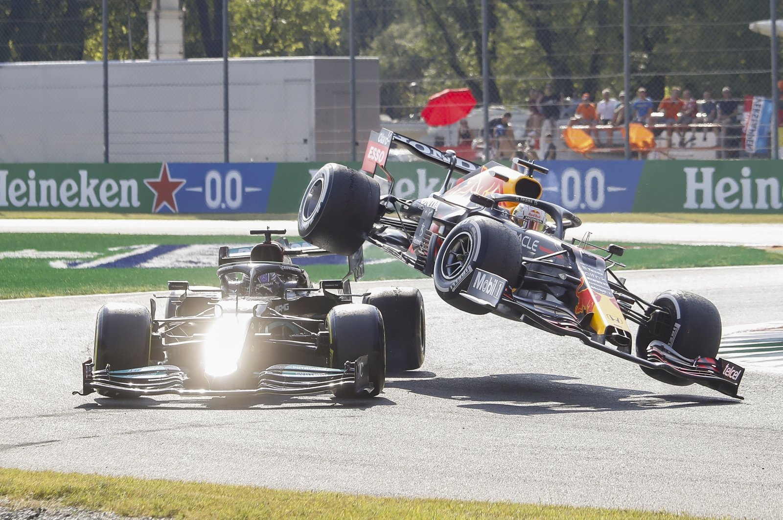 Red Bull's Dutch driver Max Verstappen (R) collides with Mercedes' British driver Lewis Hamilton (L) during the Formula One Grand Prix of Italy at Monza, Italy, Sept. 12, 2021. (EPA)