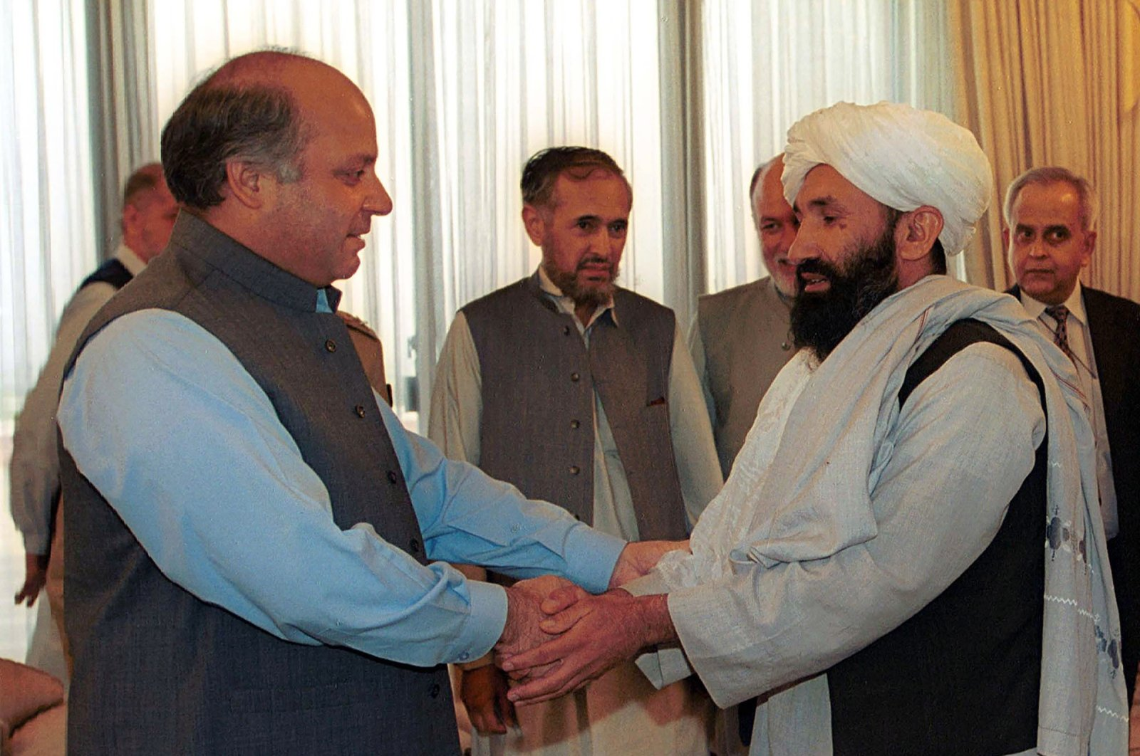 Mullah Mohammad Hasan Akhund (R), Afghanistan's then-foreign minister, is received by Pakistani then-Prime Minister Nawaz Sharif, in Islamabad, Pakistan, Aug. 25, 1999. (AP File Photo)