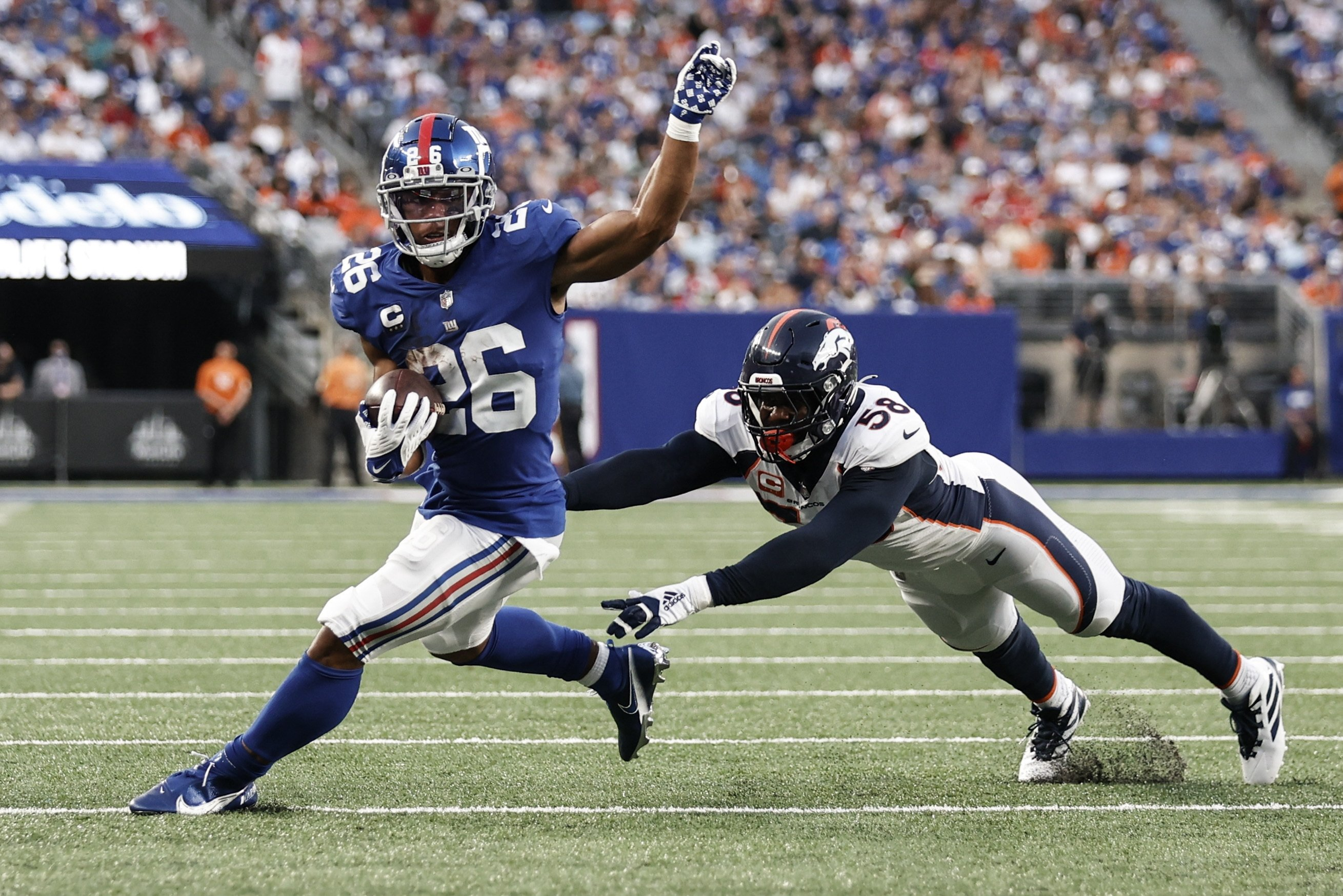 New York Giants running back Saquon Barkley (26) runs away from Denver Broncos' Von Miller (58) during the second half of the Broncos 27-13 victory, East Rutherford, New Jersey, U.S., Sept. 12, 2021. (AP Photo)