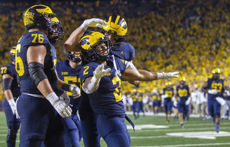 Michigan running back Blake Corum (2) celebrates a touchdown with teammates during the fourth quarter of an NCAA college football game against Washington in Ann Arbor, Michigan, U.S., Sept. 11, 2021. (AP Photo)