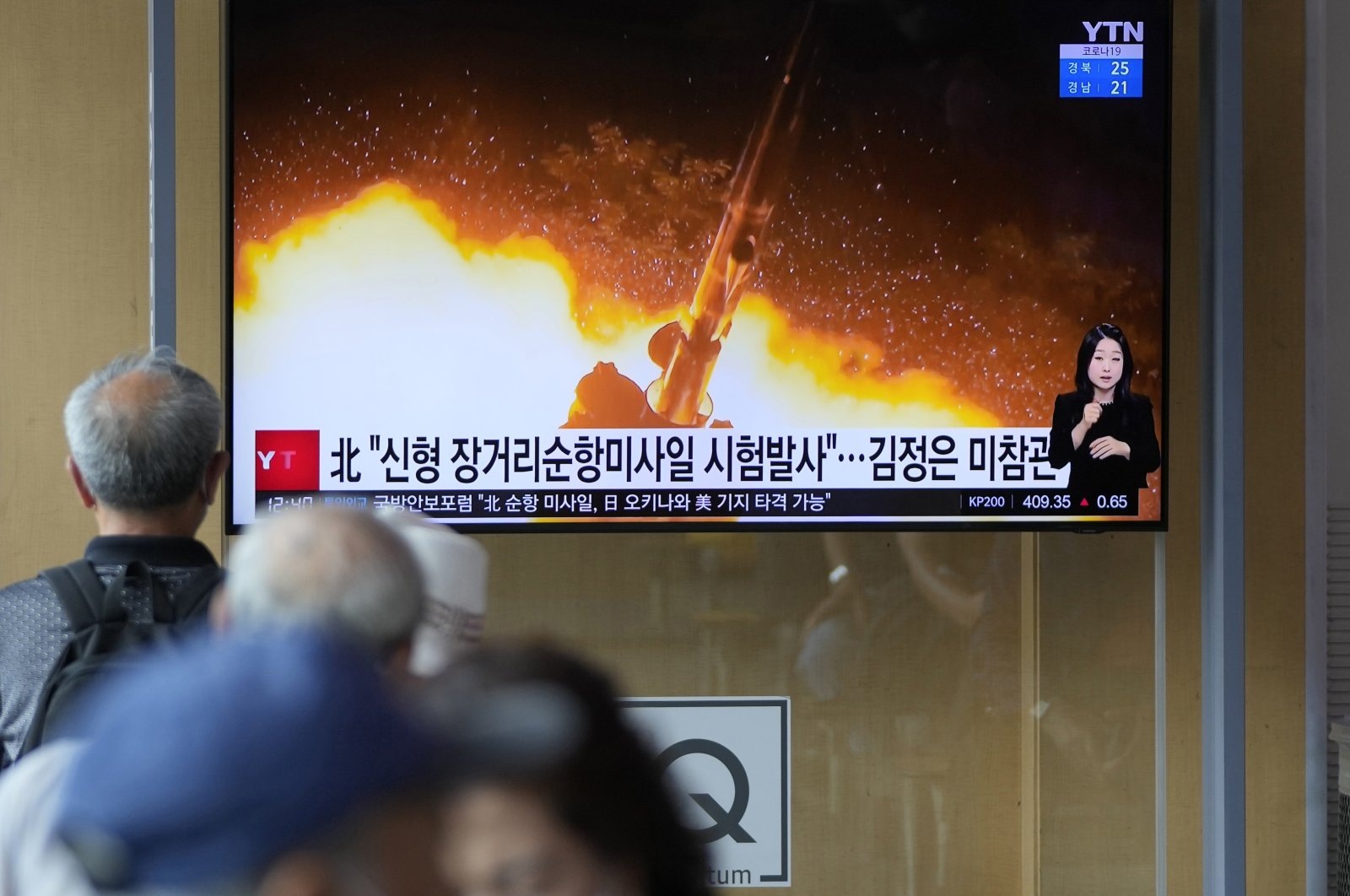 """People watch a news program that was showing part of a North Korean handout photo that says, """"North Korea's long-range cruise missiles tests,"""" in Seoul, South Korea, Sept. 13, 2021. (AP Photo)"""